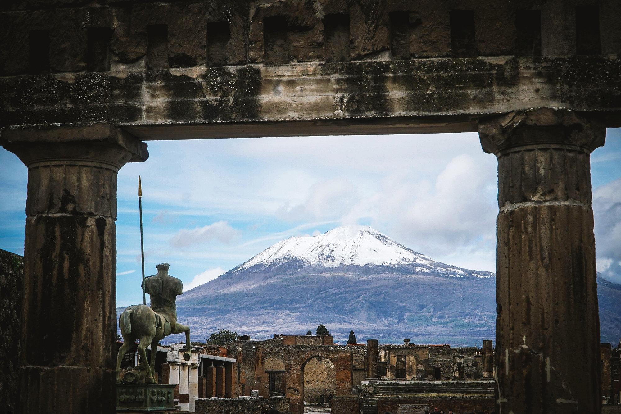 Заснеженная вершина вулкана Везувий вобрамлении руин, обнаруженных врезультате археологических раскопок города Помпеи близ Неаполя, Италия, 23 января 2019