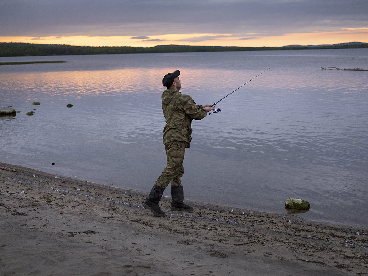 Aleksey fishing by the river, in Nikel, Russia.
