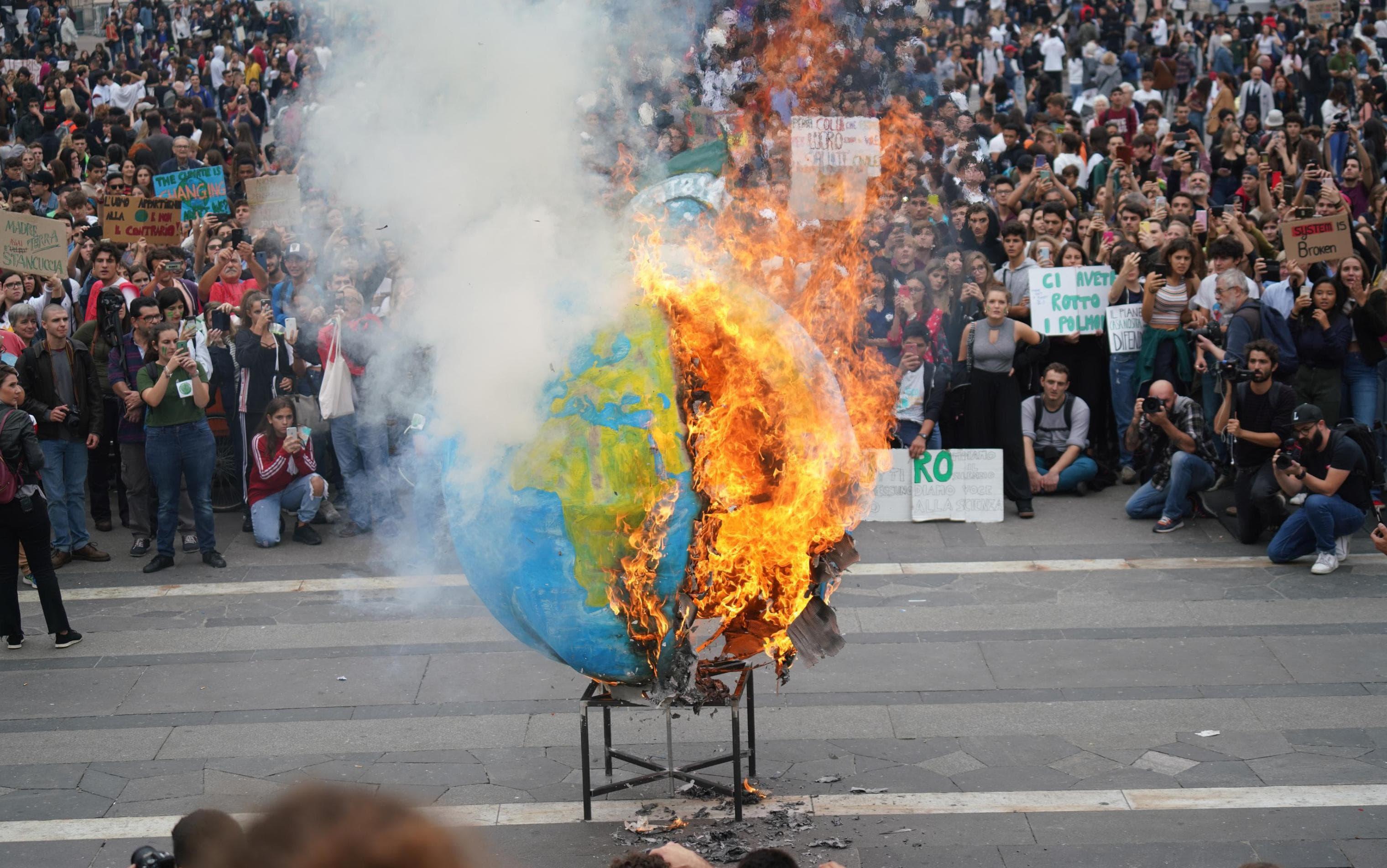 Студенты подожгли точную копию планеты Земля во время всемирной акции протеста против изменения климата вМилане, северная Италия, 27 сентября 2019 года. Протесты вдохновлены речью 16-летней активистки Греты Тунберг насаммите Организации Объединенных Наций.