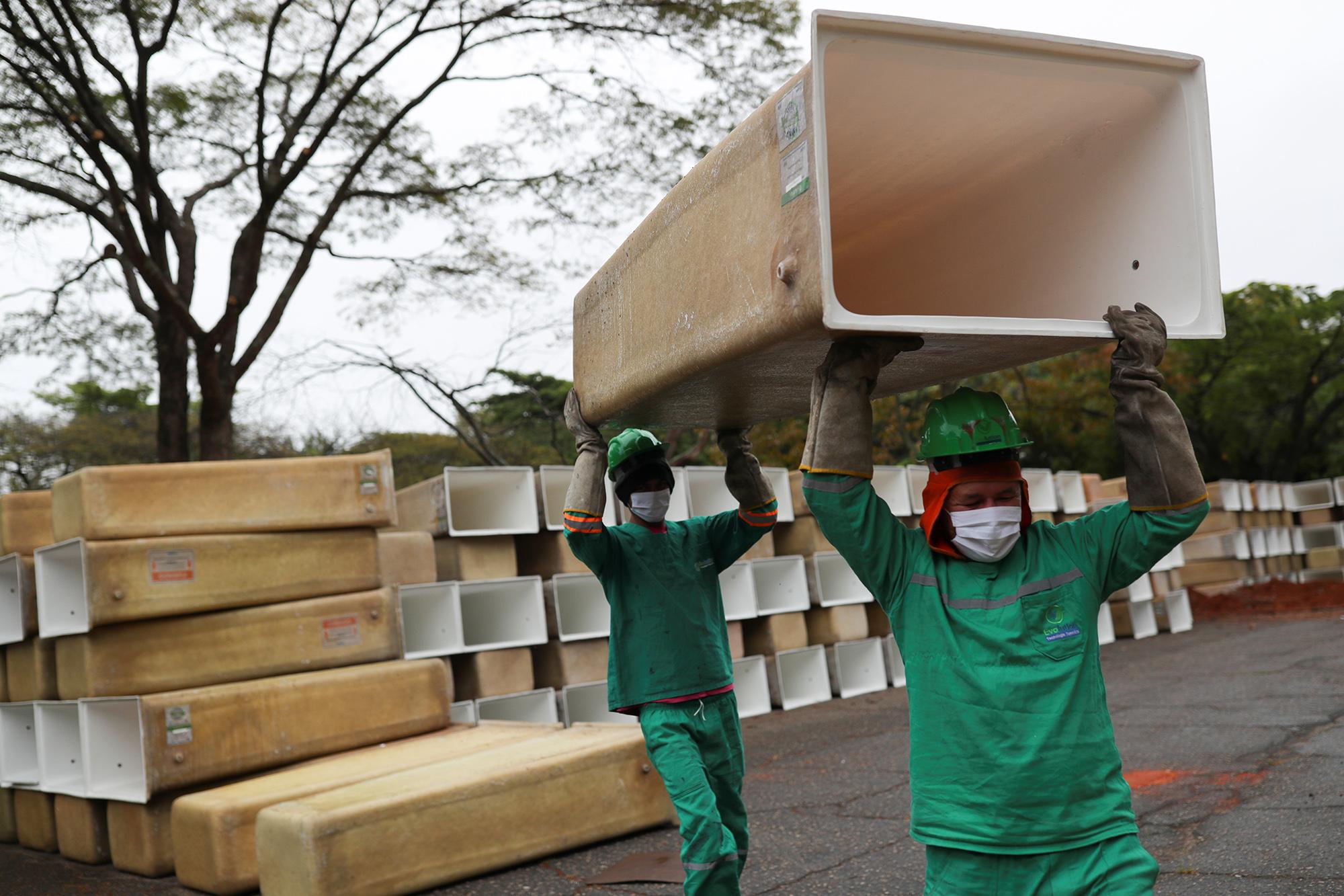 Мужчины несут коробки длягробов накладбище вСан-Паулу.