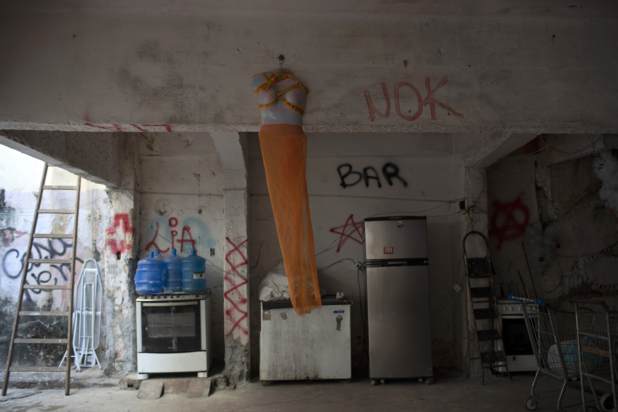 A half torso mannequin decorated with an orange veil hangs from a beam backdropped by donated items in the courtyard of the squat known as Casa Nem, occupied by members of the LGBTQ community who are in self-quarantine as a protective measure against the new coronavirus, in Rio de Janeiro, Brazil, Wednesday, July 8, 2020. They receive food donations as well and are barred from leaving unless facing medical emergency or other exceptional circumstances.