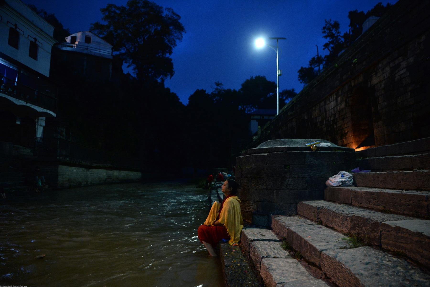Жительница Катманду купается вреке Багмати вчастичное лунное затмение, Непал
