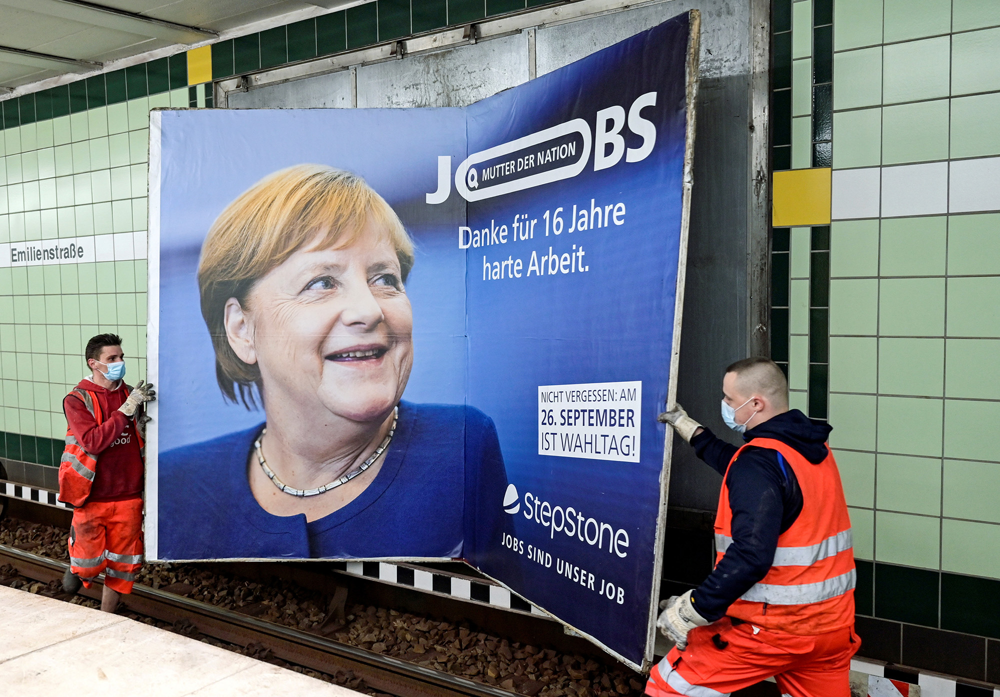 Workers remove an advertisement showing German Chancellor Angela Merkel with a slogan that reads