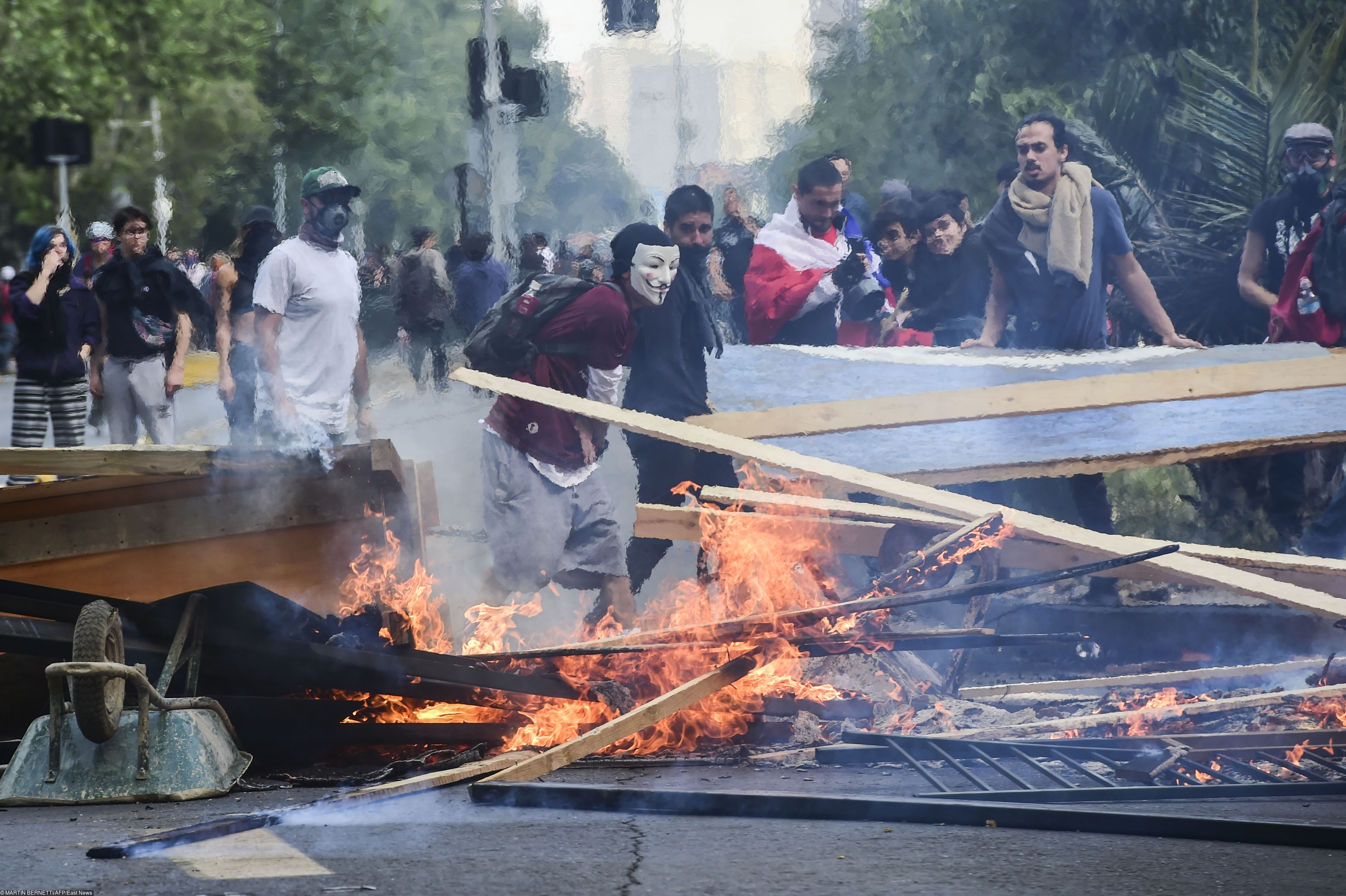 Demonstrators set up barricades during clashes between protesters and the riot police in Santiago, on October 19, 2019. - Chile's president declared a state of emergency in Santiago Friday night and gave the military responsibility for security after a day of violent protests over an increase in the price of metro tickets. (Photo by Martin BERNETTI / AFP)