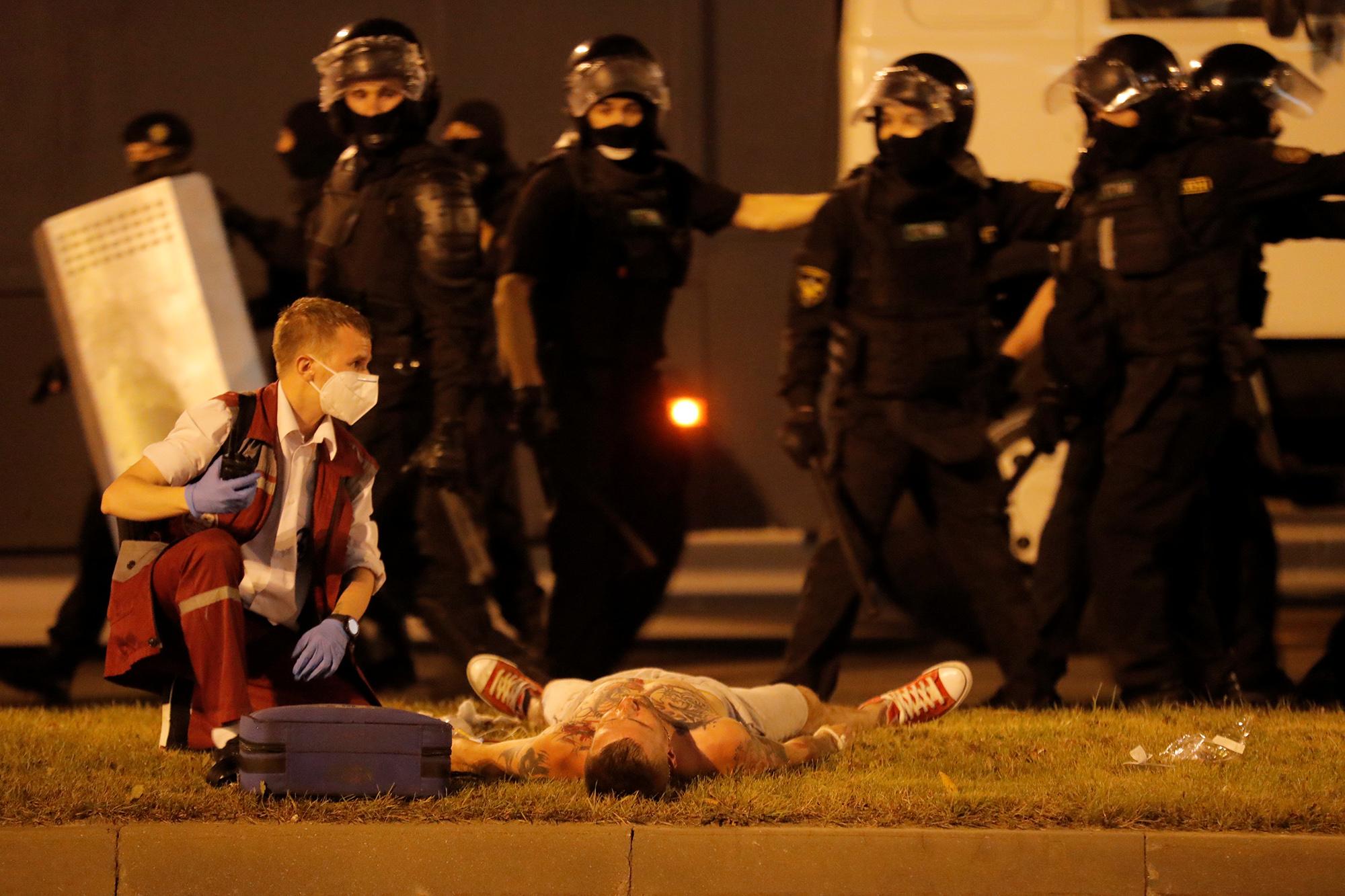 Пострадавший всхватке сполицией протестующий лежит натраве иждет, когда ему окажут помощь