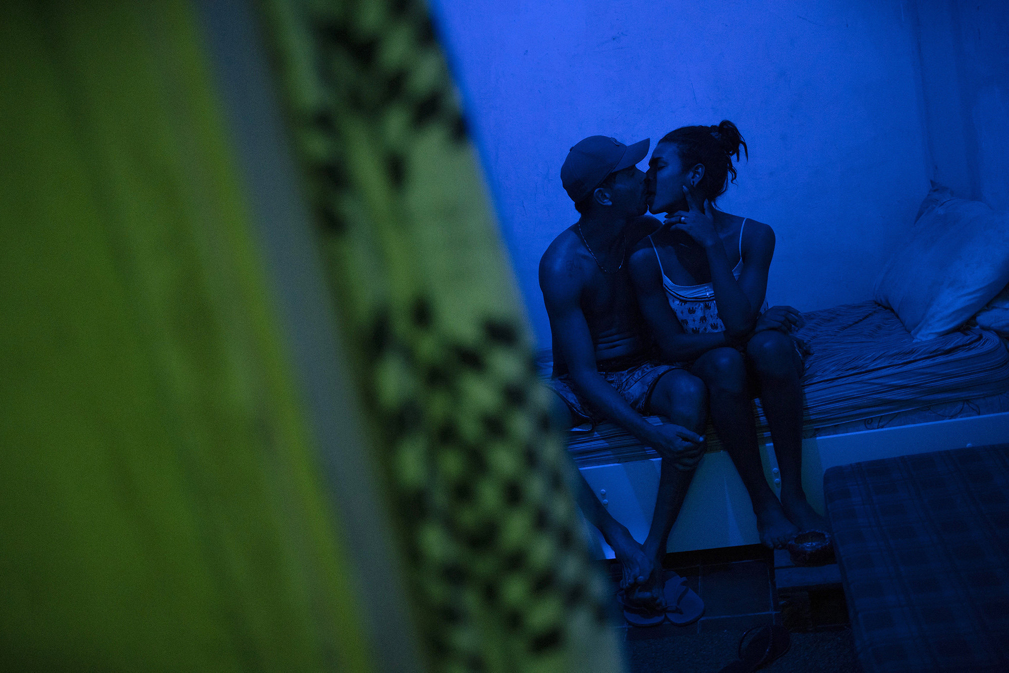 Richard Santos and his partner Lia kiss in their bedroom in the squat known as Casa Nem, occupied by members of the LGBTQ community who are in self-quarantine as a protective measure against the new coronavirus, in Rio de Janeiro, Brazil, Saturday, May 23, 2020. Several years ago Casa Nem became a shelter for LGBTQ victims of violence and those who, rejected by their families, have nowhere to live.