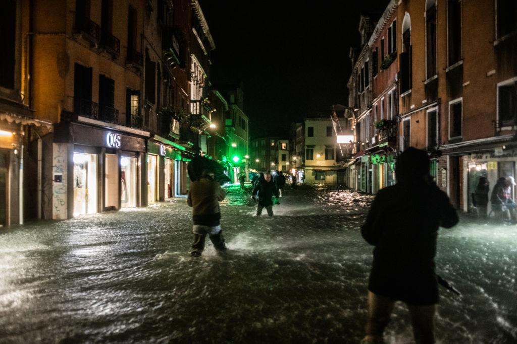 Люди гуляют позатопленному городу