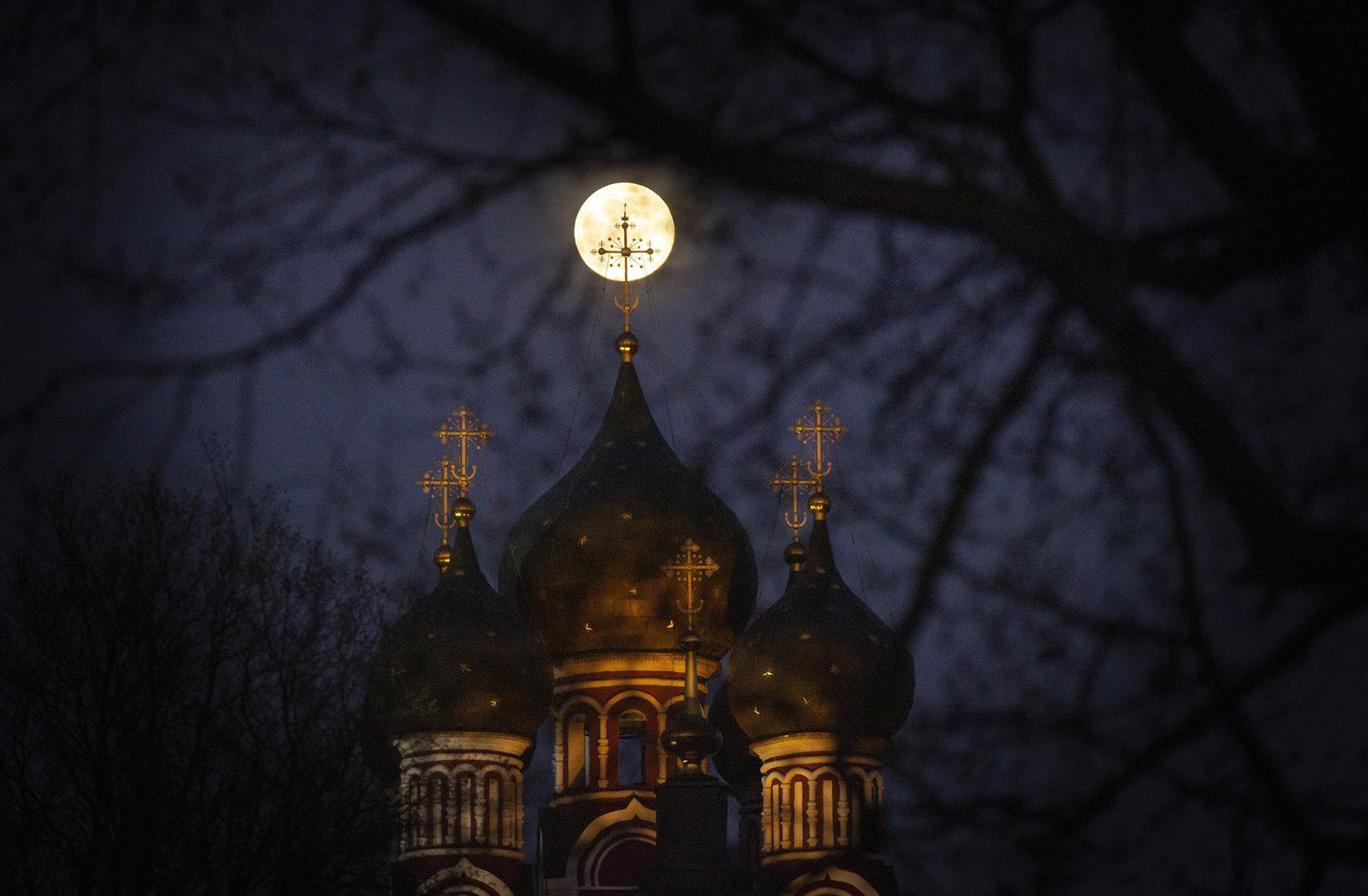 Суперлуна освещает крест церкви вМоскве