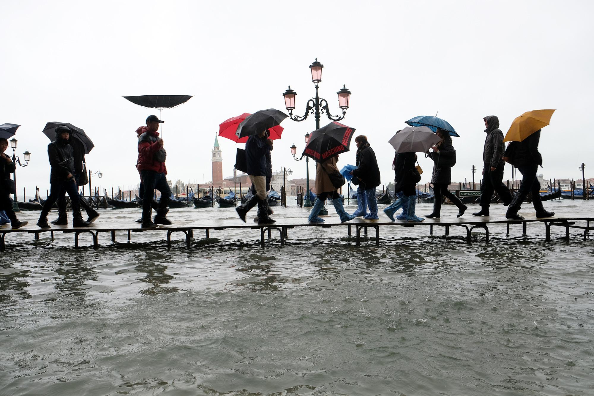 Люди идут поподиуму, установленному назатопленной площади Святого Марка