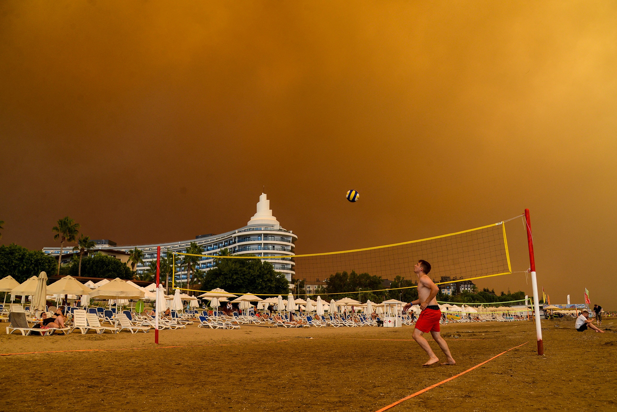 Dark smoke drifts over a hotel complex during a massive forest fire which engulfed a Mediterranean resort region on Turkey's southern coast near the town of Manavgat, on July 29, 2021. - At least three people were reported dead on July 29, 2021 and more than 100 injured as firefighters battled blazes engulfing a Mediterranean resort region on Turkey's southern coast. Officials also launched an investigation into suspicions that the fires that broke out Wednesday in four locations to the east of the tourist hotspot Antalya were the result of arson.