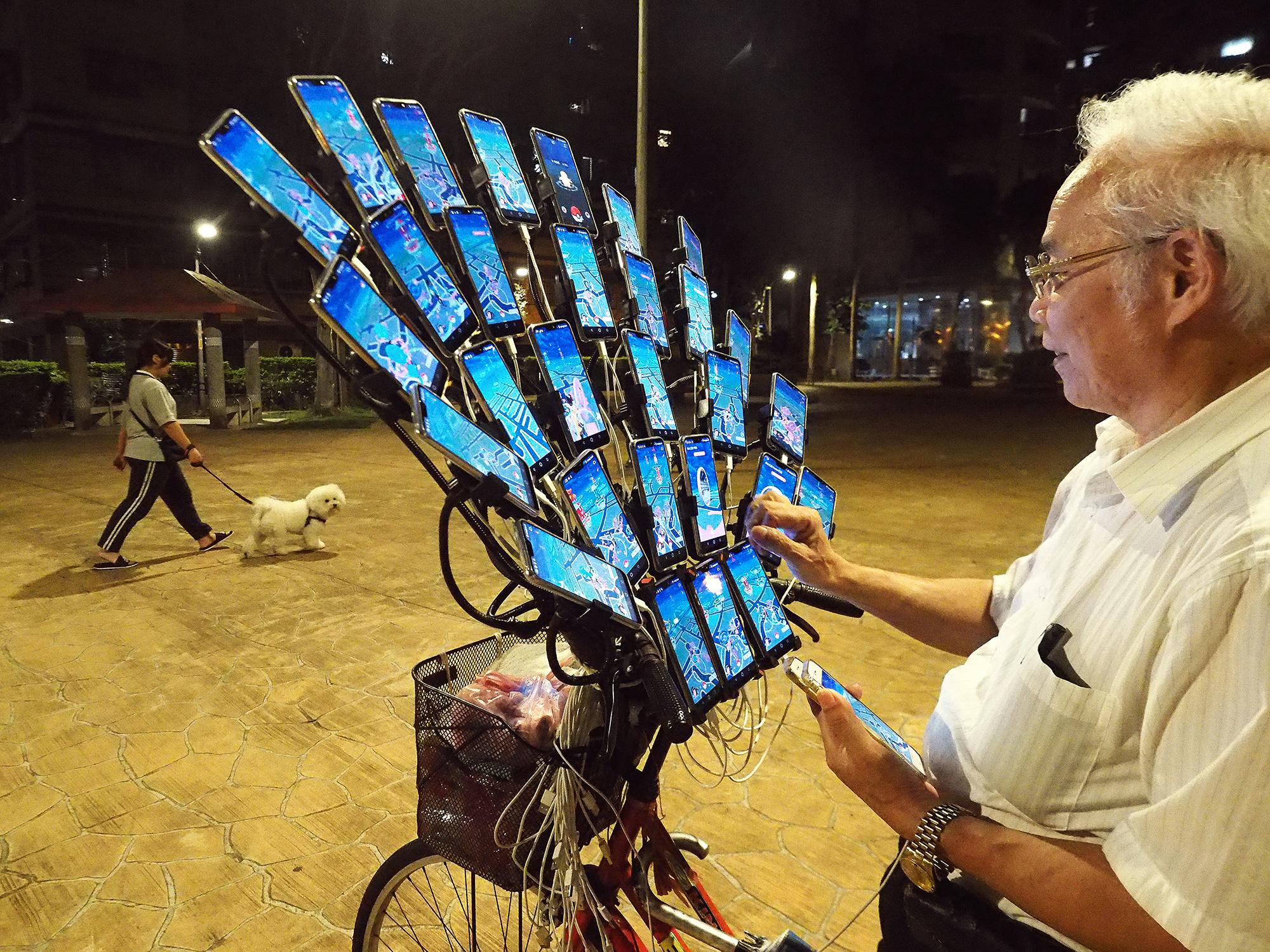 Чен Сан-юань, 70-летний мастер фэн-шуй, а также 29 смартфонов и2 портативных телефона, установленные наего велосипеде, — они нужны ему, чтобы ловить покемонов. Чен подсел наPokemon Go в2016 году, когда внук научил его играть вэту игру. Теперь все свое свободное время Чен проводит, ловя покемонов наулицах или впарках, иногда оставаясь наулице до4 часов утра. Он получил прозвище «Дядя Покемон» идаже стал знаменитостью: тайваньская ASUS TeK Computer Inc. пригласила его стать представителем своего смартфона Zenfone Max Pro M2. Снимок сделан вНью-Тайбэе, Тайвань, 14 мая 2019 года