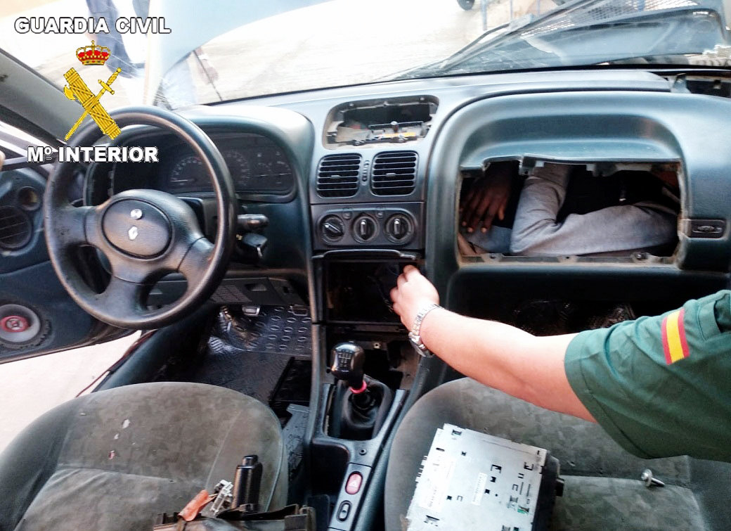 На этом снимке, предоставленном 27 мая 2019 года «Гражданской гвардией Испании» иснятом вМелилье, изображен член гвардии, обнаруживший отсек, которы был построен заприборной панелью автомобиля, — там находится мигрант изАфрики. Три африканца, втом числе 15-летняя девочка идвое мужчин (20 лет и21 год), были найдены зажатыми вподобных отсеках заприборными панелями исиденьями напограничной территории между Марокко иИспанией. Всех троих нашли в3 разных машинах натерритории между Марокко ииспанской Мелильей втечение всего лишь трех часов.