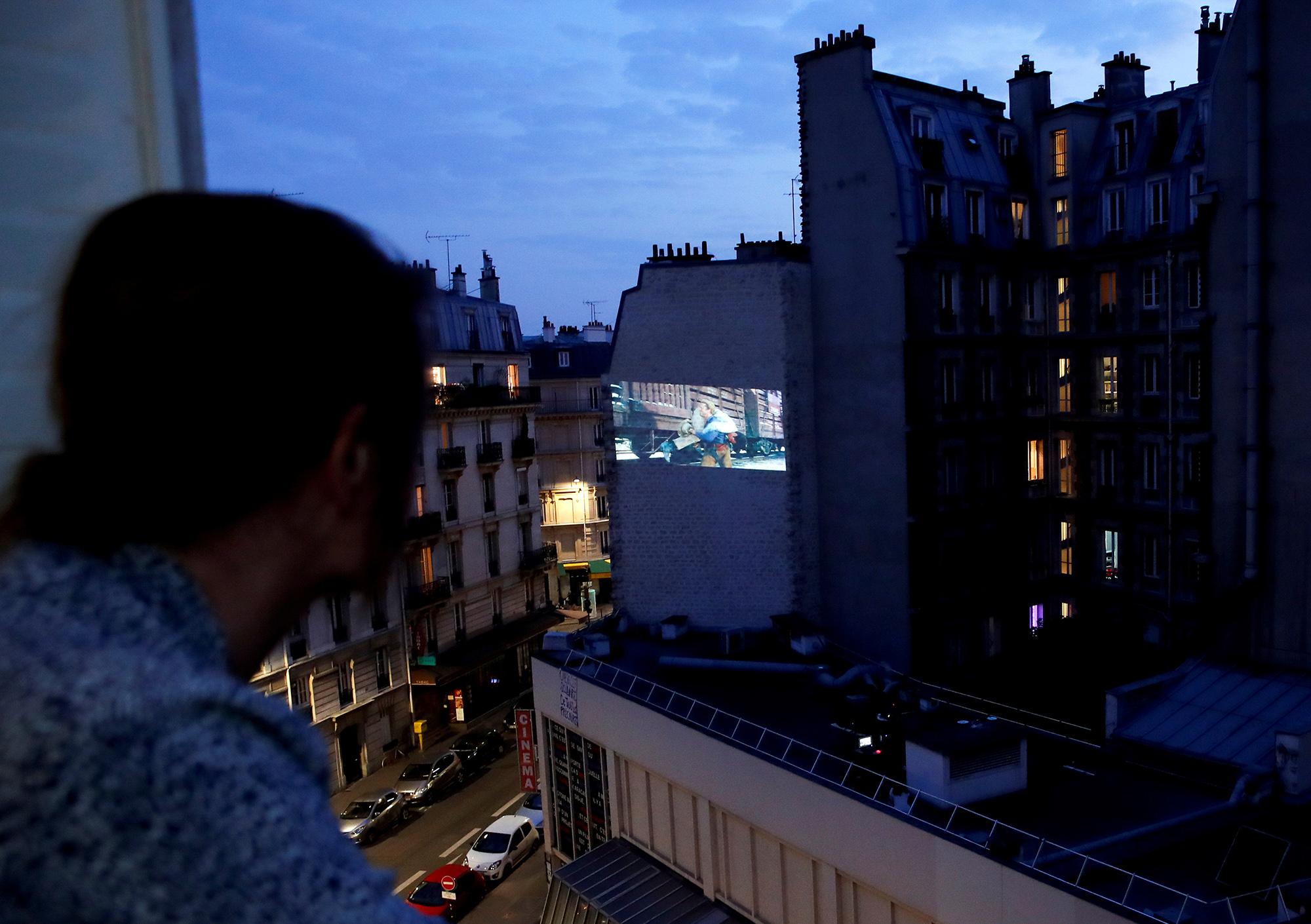 Писательница Кристина Давенье смотрит вестерн «Человек беззвезд» режиссера Кинга Видора, который поинициативе Ассоциации Домашнего Кино проецируют настену жилого дома во время карантина покоронавирусу Covid-19 вПариже. 24 апреля 2020