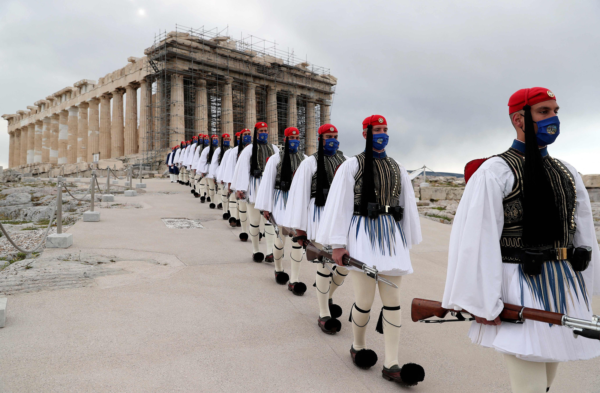 25 марта 2021 года, солдаты президентской гвардии проходят передхрамом Парфенон навершине Акрополя после церемонии поднятия греческого флага вАфинах. Греция отмечает двухсотлетие начала войны занезависимость против Османской империи