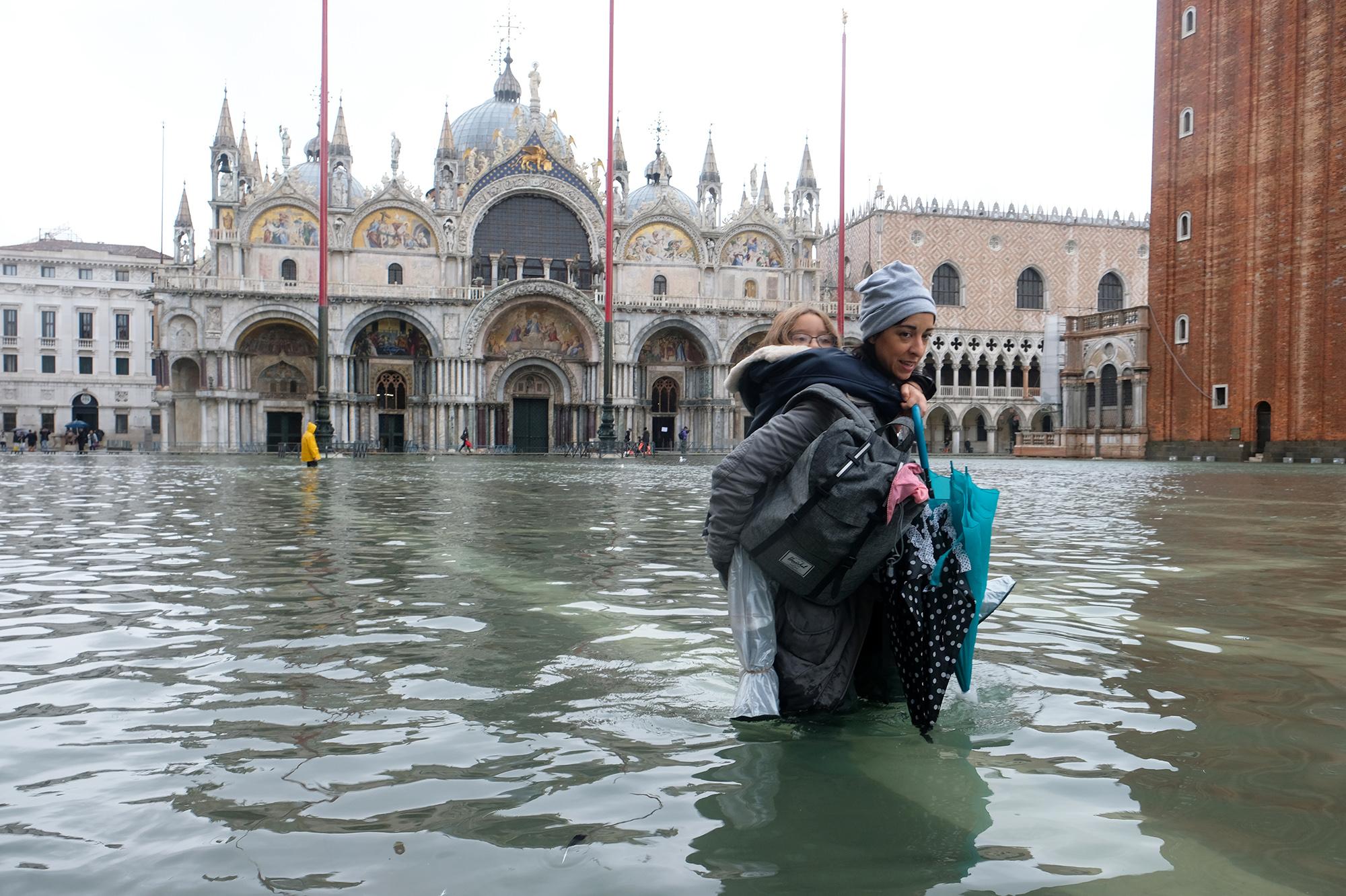 Женщина сребенком пытаются пройти череззатопленную площадь Святого Марка
