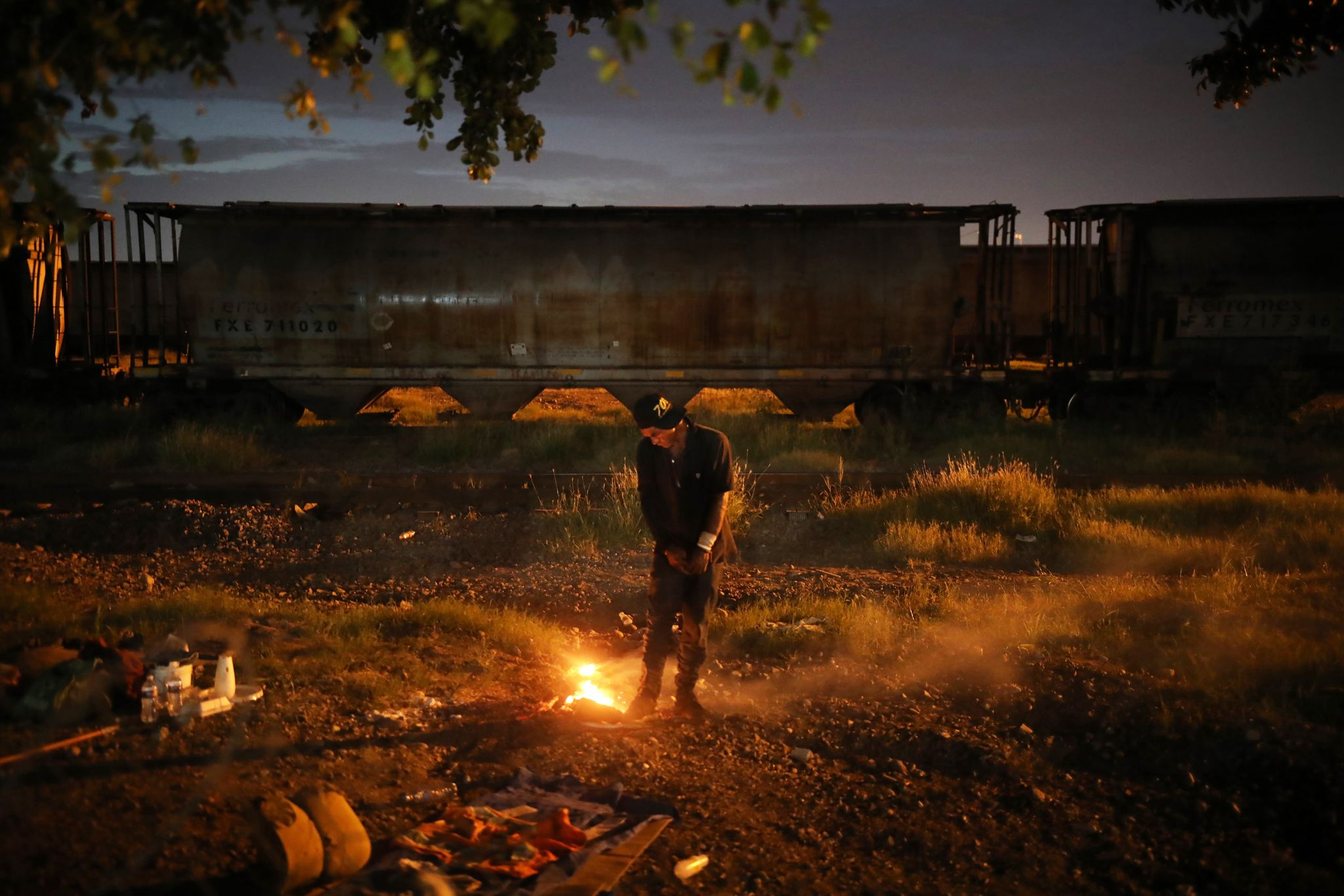A drug addict warms himself at a trash fire, in the waste ground next to the Malverde shrine