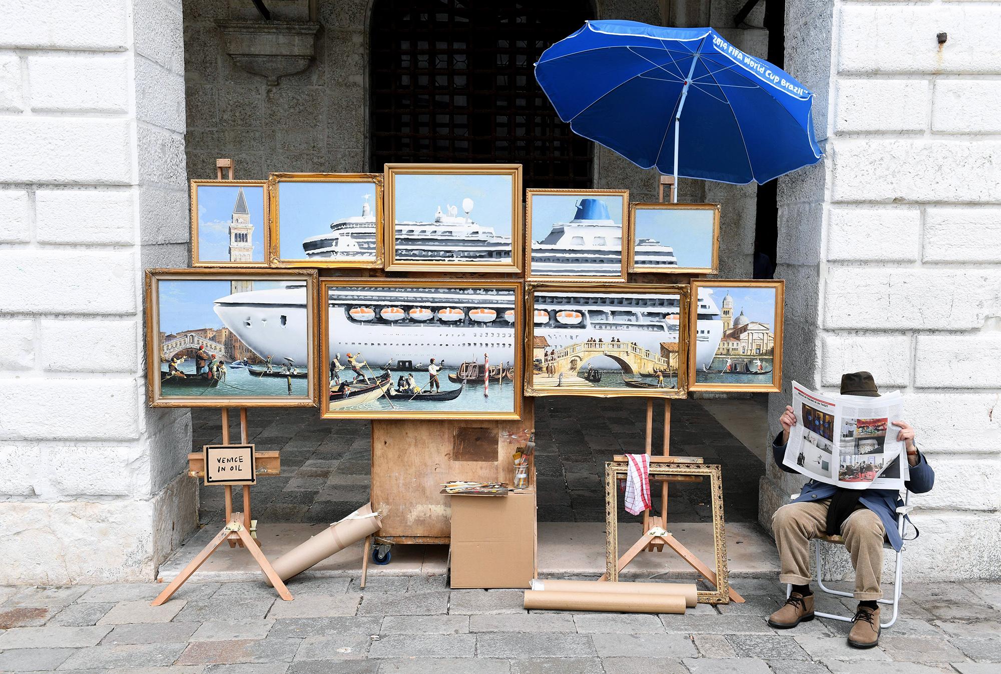 На фото — неизвестный человек наБиеннале вВенеции  (предположительно — британский уличный художник Бэнкси) рядом сгруппой картин подназванием «Венеция вмасле», изображающих огромный круизный лайнер, окруженный крошечными венецианскими гондолами. Бэнкси опубликовал винстаграме видео, где показывает, как он монтирует эту несогласованную свластями города инсталляцию. Полиция попросила человека сфото немедленно убрать все картины.