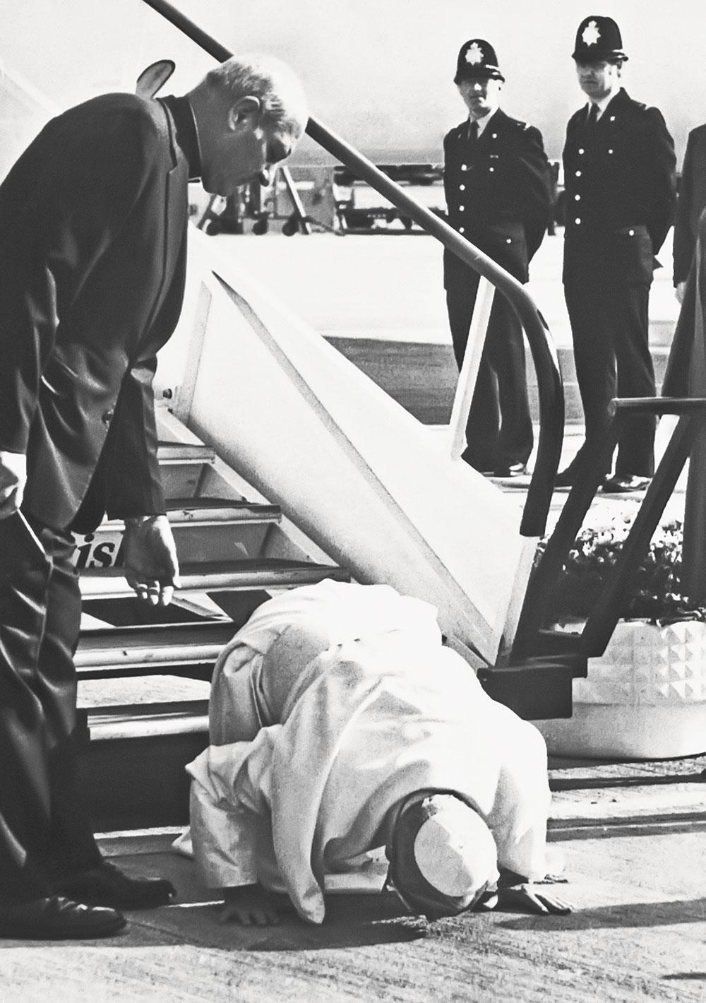 Вверху: Иоанн Павел II во время дипломатического визита целует землю Британии. Справа отнего архиепископ Марцинкус