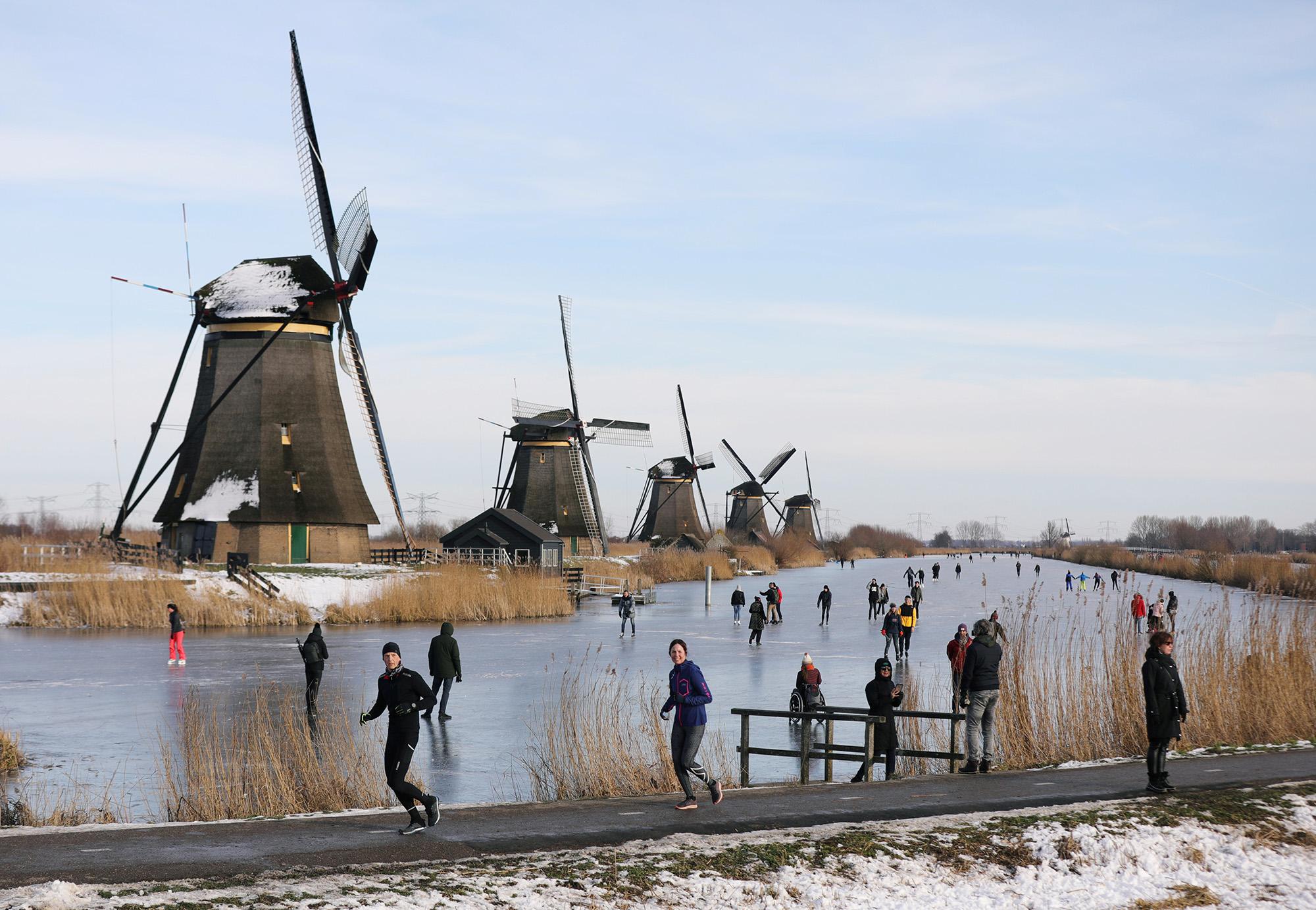 Первые занесколько лет заморозки частично заморозили каналы вголландских городах. Нафото жители деревни Киндердейк катаются наконьках.