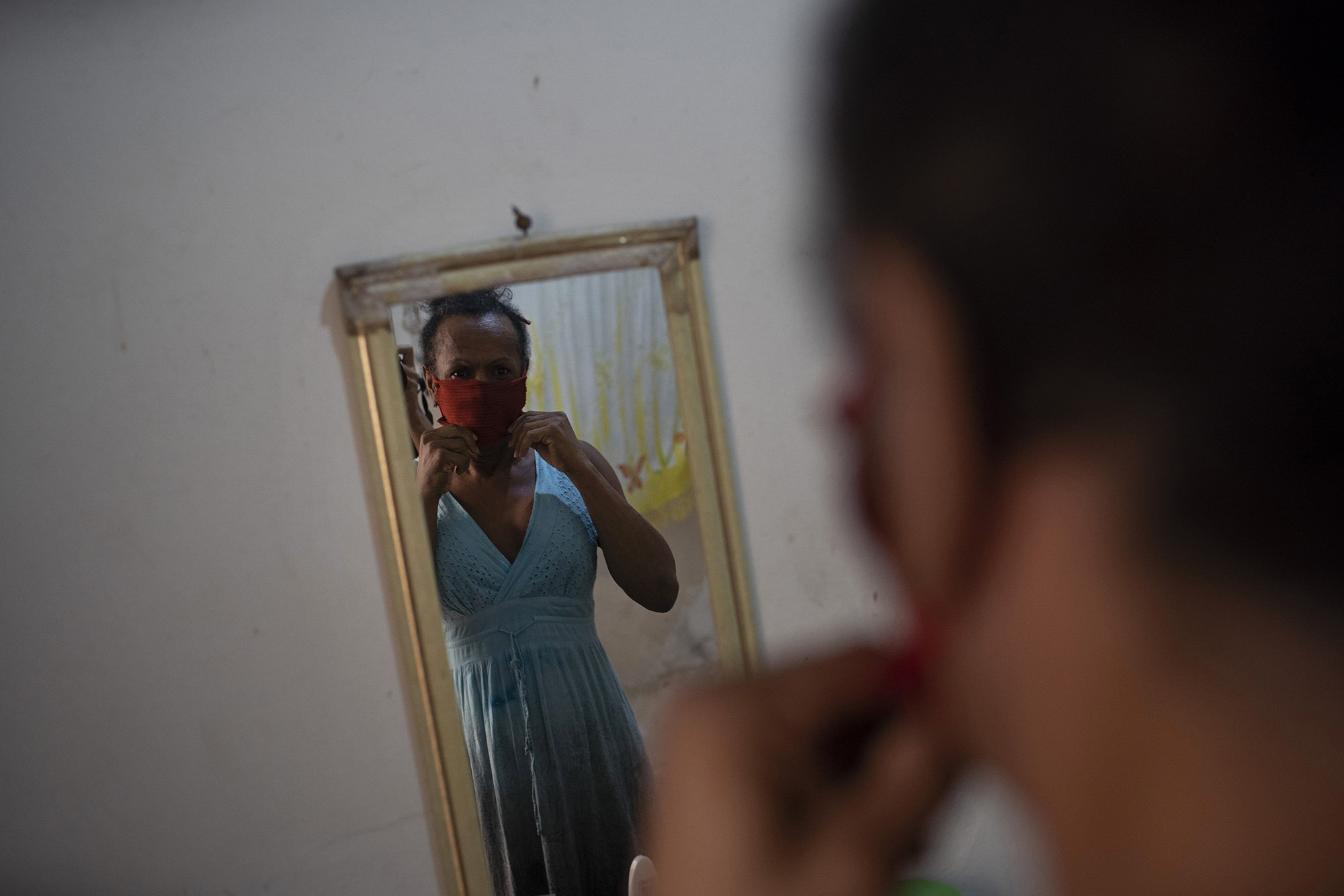 Transgender Claudinha is reflected in a mirror as she puts on a protective face mask inside her room at the squat known as Casa Nem, in Rio de Janeiro, Brazil, Wednesday, July 8, 2020. The six-floor building is home to about 50 LGBTQ people riding out the new coronavirus pandemic behind closed doors.