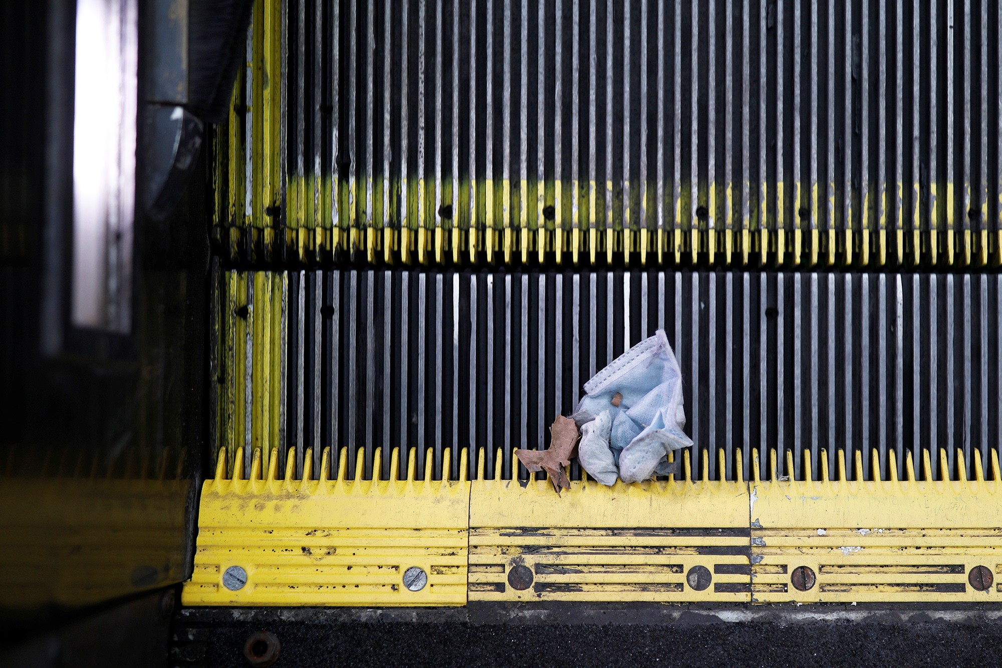 A discarded face mask is caught in the grooves of a moving escalator at the Dupont Circle Metro underground train station, as Mayor Muriel Bowser declared a State of Emergency due to the coronavirus disease (COVID-19) in Washington, U.S., March 16, 2020. Tom Brenner/REUTERS
