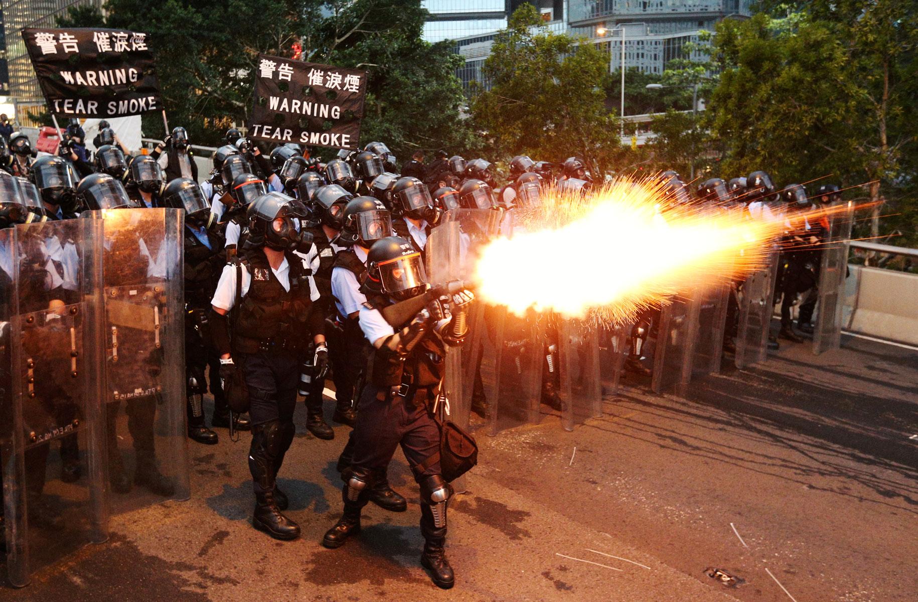 Полицейские распыляют слезоточивый газ против демонстрантов вГонконге, выступающих против принятия закона обэкстрадиции. Местные жители считают, что власти Китая будут использовать этот закон дляпреследования политических активистов