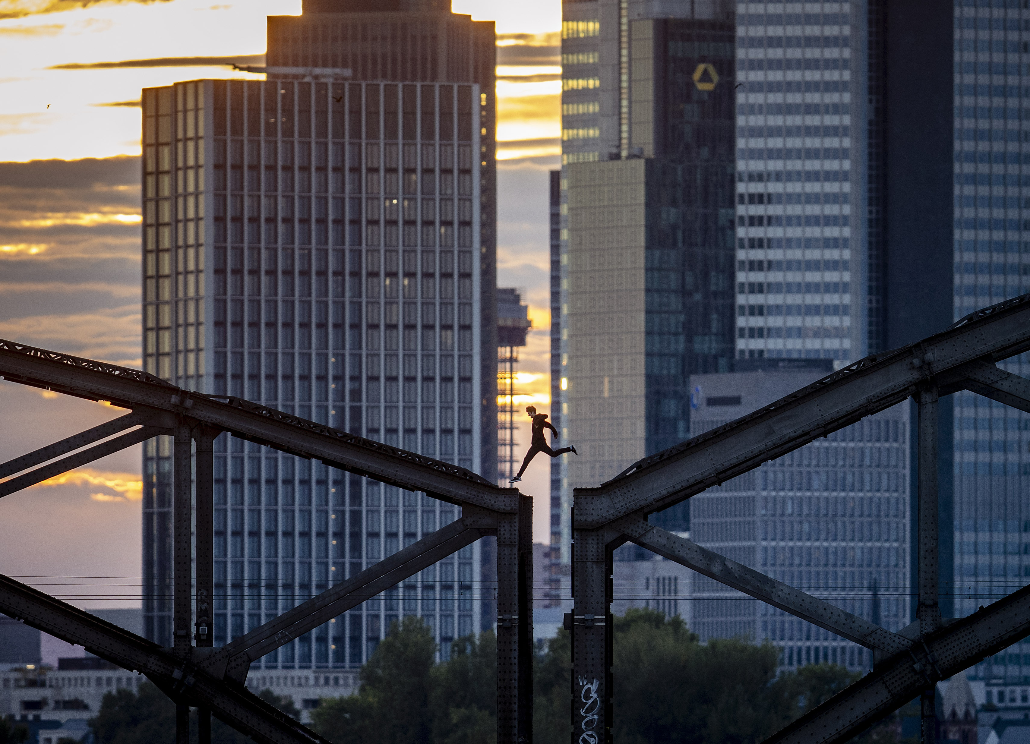 A parkour runner jumps on a railway bridge with the buildings of the banking district in background in Frankfurt, Germany, Wednesday, Sept. 9, 2020. (AP Photo/Michael Probst)