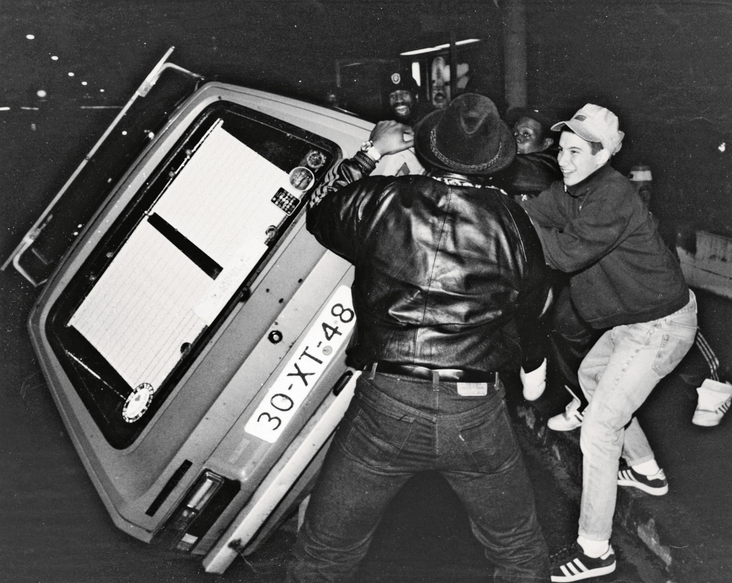 Адам Хоровиц (лицом ккамере) ифанаты Beastie Boys переворачивают машину во время гастролей группы вШвейцарии, ок. 1987 г.