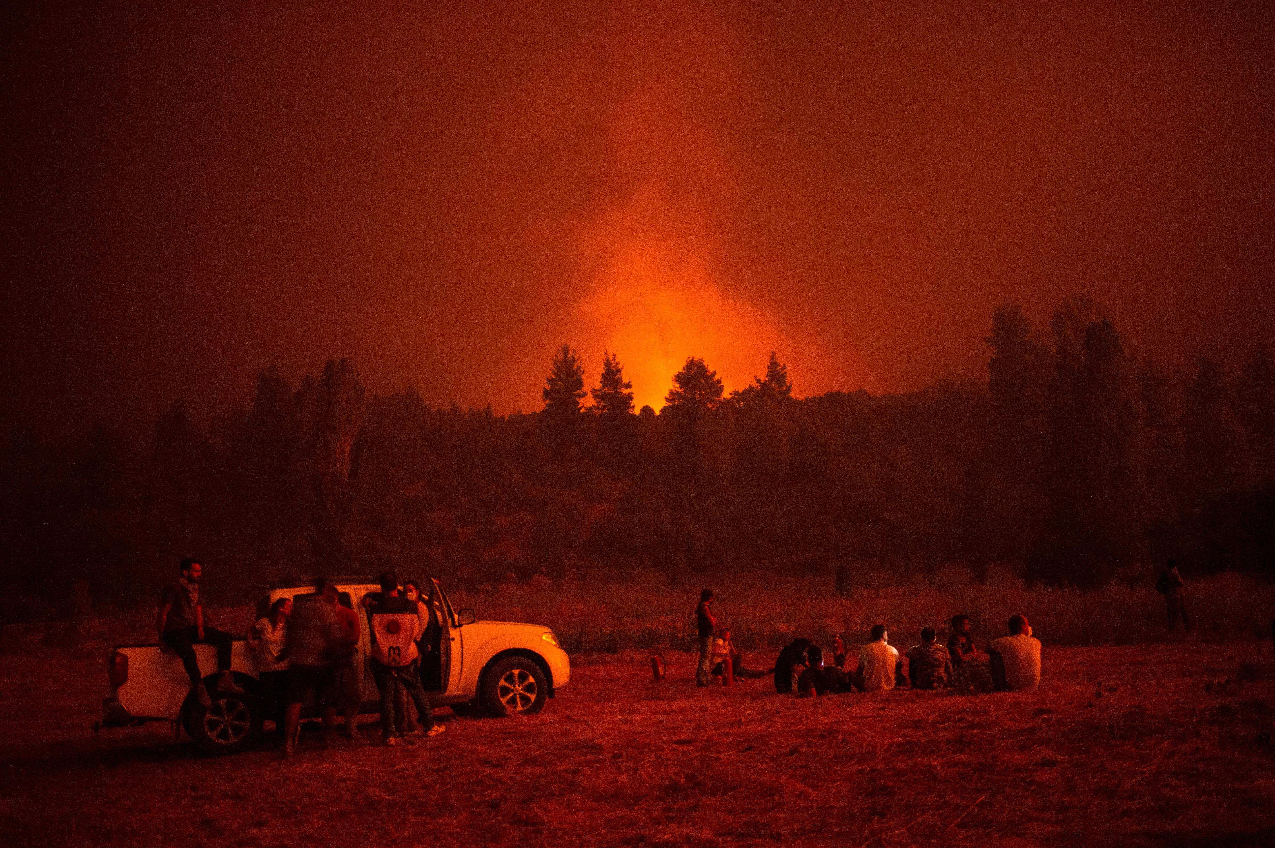 Молодежь иволонтеры собираются воткрытом поле иждут, чтобы помочь пожарным во время лесного пожара рядом сдеревней Каматриадес, недалеко отИстиа, северная Эвия (Эвбея), 9 августа 2021 г.