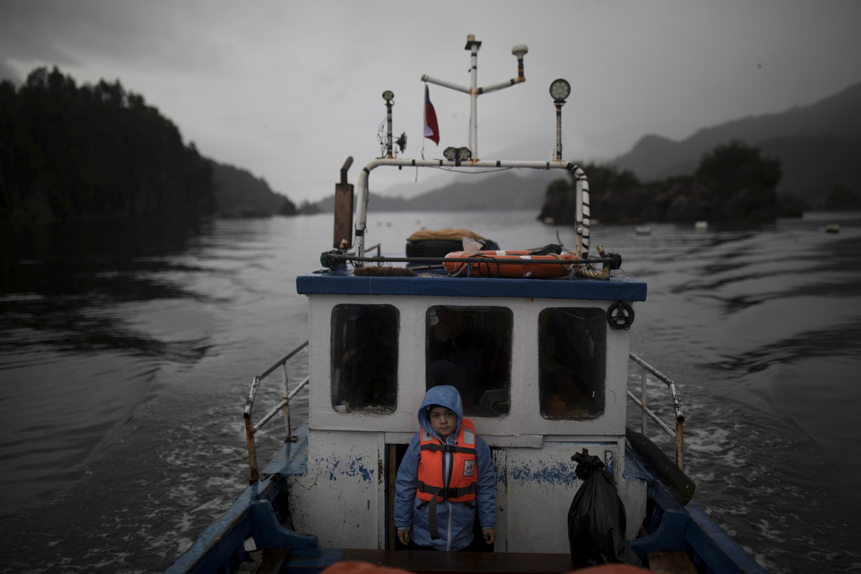 Диего Герреро наотцовской лодке плывет вшколу имени Джона Ф. Кеннеди вдеревне Сотомо, недалеко отгорода Кочамо, регион Лос-Лагос, Чили, 6 августа 2021 года.