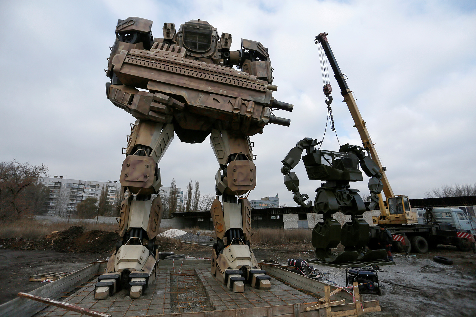 Robots made by local enthusiasts and employees of an automobile repair workshop are seen during installation works on the outskirts of the rebel-controlled city of Donetsk, Ukraine, November 26, 2020. According to creators, who plan to open a robotics engineering park, 13-metre and 6-metre-high sculptures featuring transformer robots were made of waste metal including car components and weigh about 4 and 2 tonnes respectively. REUTERS/Alexander Ermochenko