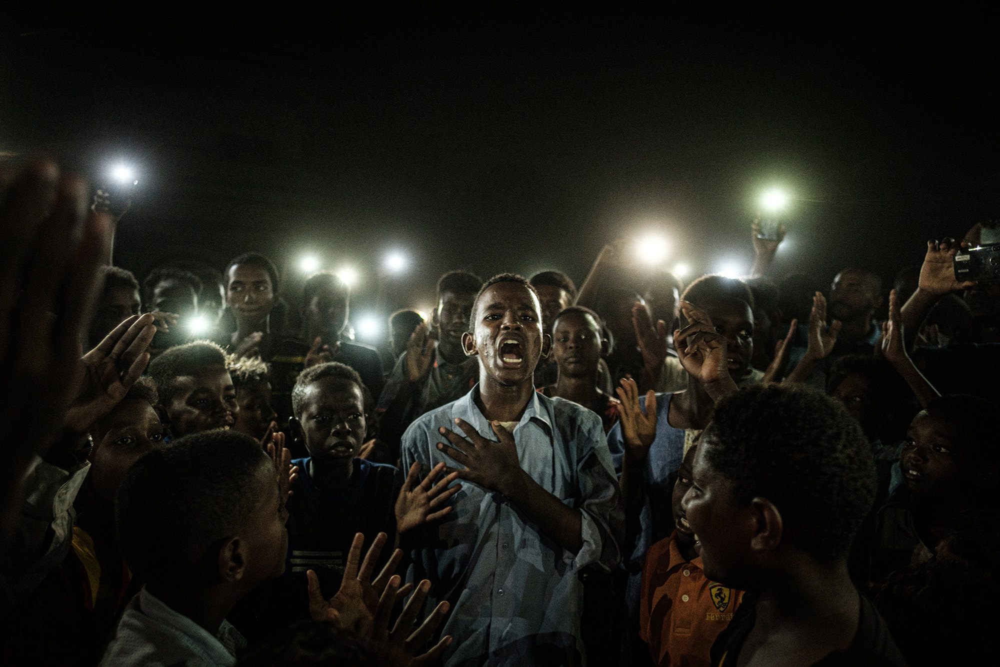 Caption: A young man, illuminated by mobile phones, recites protest poetry while demonstrators chant slogans calling for civilian rule, during a blackout in Khartoum, Sudan, on 19 June 2019.Story: Protests in Sudan began in December 2018 and spread rapidly throughout the country. By April 2019, protesters were staging a sit-in close to army headquarters in the capital Khartoum, and demanding an end to the 30-year rule of dictator Omar al-Bashir. On 11 April, al-Bashir was removed from office in a military coup, and a transitional military government was established. Protests continued, calling for power to be handed to civilian groups. On 3 June, government forces opened fire on unarmed protesters. Scores of people were killed and many more subject to further violence. Three days later the African Union suspended Sudan, in the midst of widespread international condemnation of the attack. The authorities sought to defuse protests by imposing blackouts, and shutting down the internet. Protesters communicated by text message, word of mouth and using megaphones, and resistance to military rule continued. Despite another severe crackdown on 30 June, the pro-democracy movement was eventually successful in signing a power-sharing agreement with the military, on 17 August.