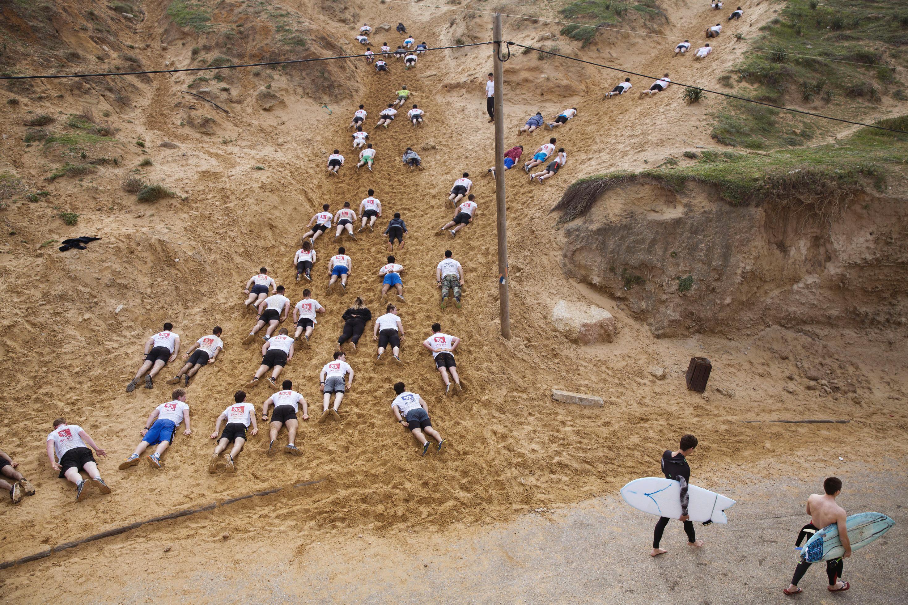 Двое серферов проходят мимо старшеклассников, которые готовятся кслужбе визраильской армии, тренируясь ползти икарабкаться попеску, Герцлия, 1 февраля.