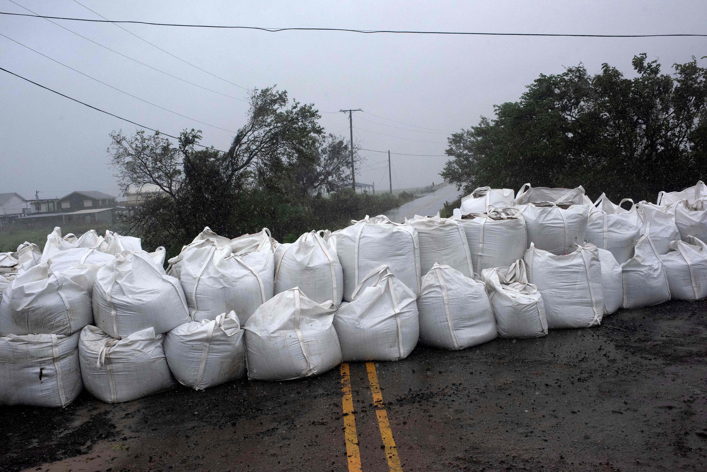 Дождь заливает мешки спеском вштате Луизиана, незадолго доначала урагана, 29 августа 2021 года.