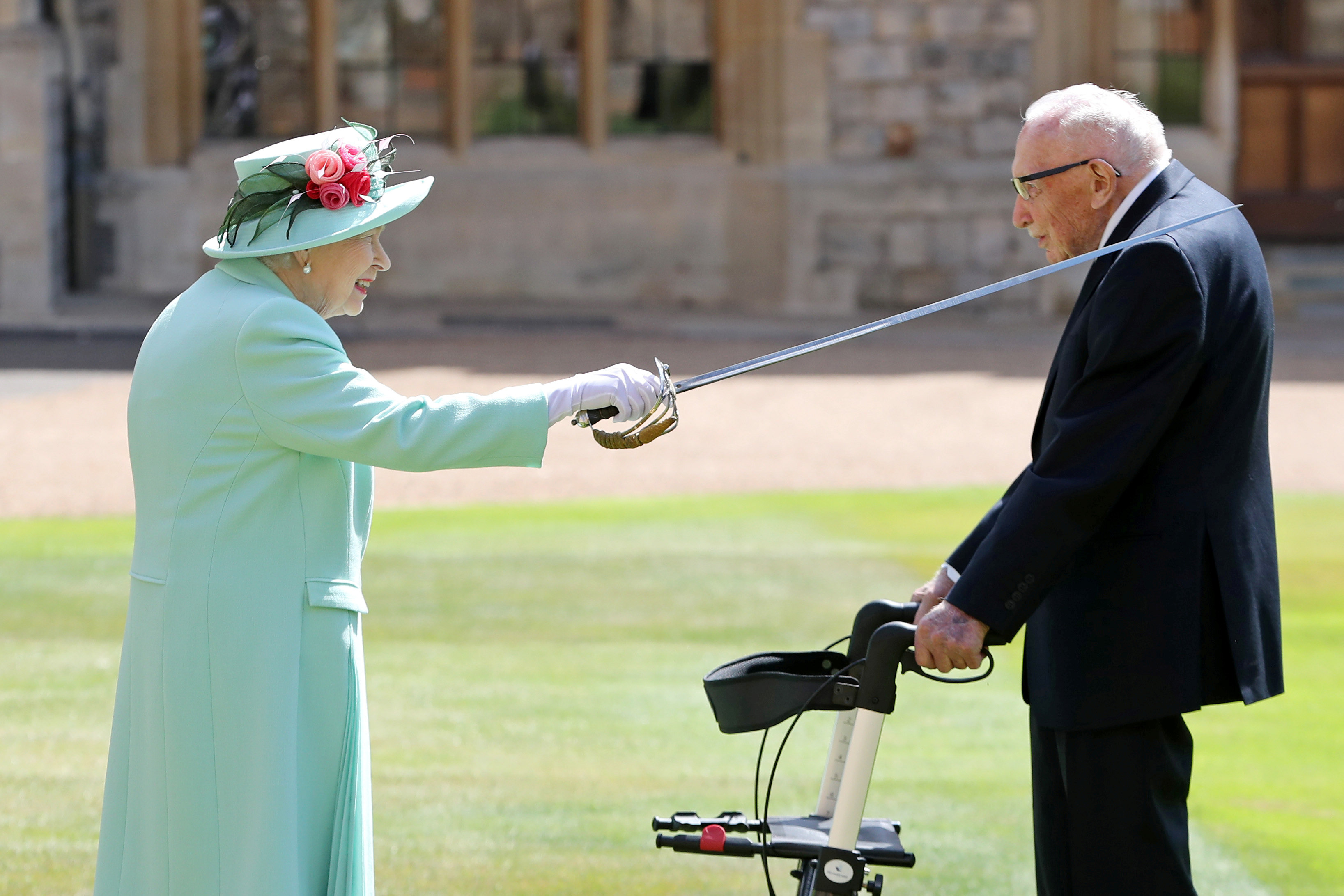 Britain's Queen Elizabeth awards Captain Tom Moore with the insignia of Knight Bachelor at Windsor Castle, in Windsor, Britain July 17, 2020