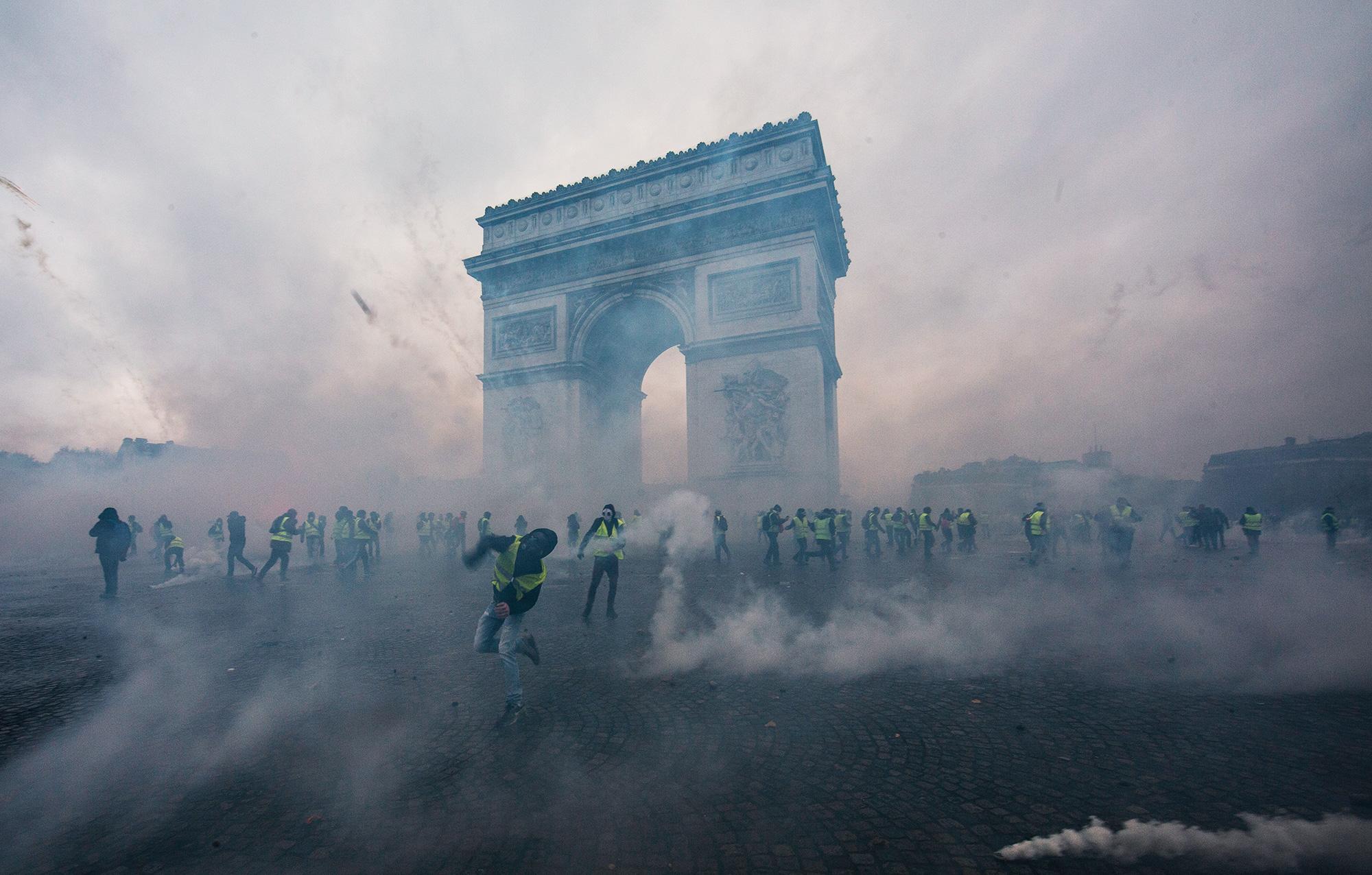 Облако слезоточивого газа вокруг протестующих исиловиков во время демонстрации «Желтых жилетов» возле Триумфальной арки 1 декабря 2018 вПариже