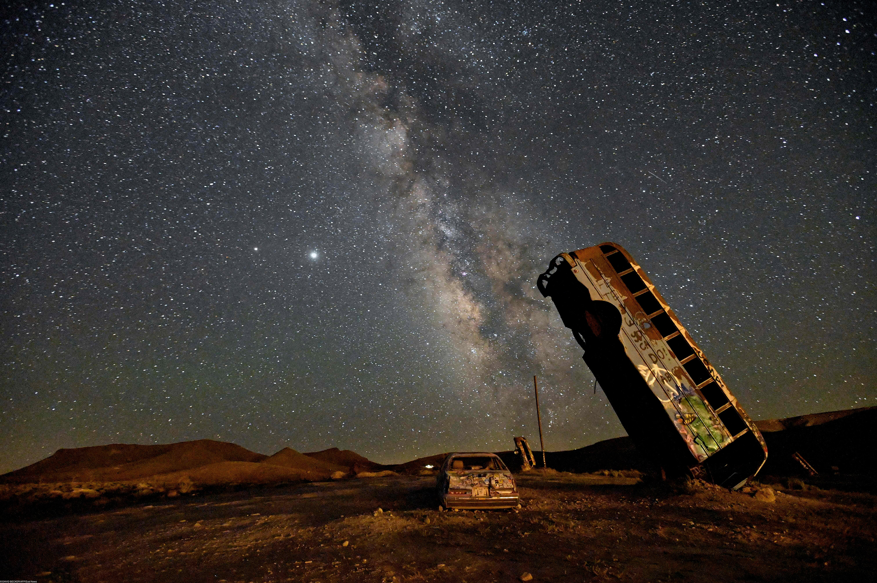 The Milky Way galaxy is seen in the sky above the International Car Forest of the Last Church in Goldfield, Nevada on July 18, 2020. - The roadside attraction, created in 2002 by Mark Rippie, has over 36 automobiles including cars, trucks, vans and buses that have been balanced on their ends or stacked on top one of another. (Photo by David Becker / AFP)