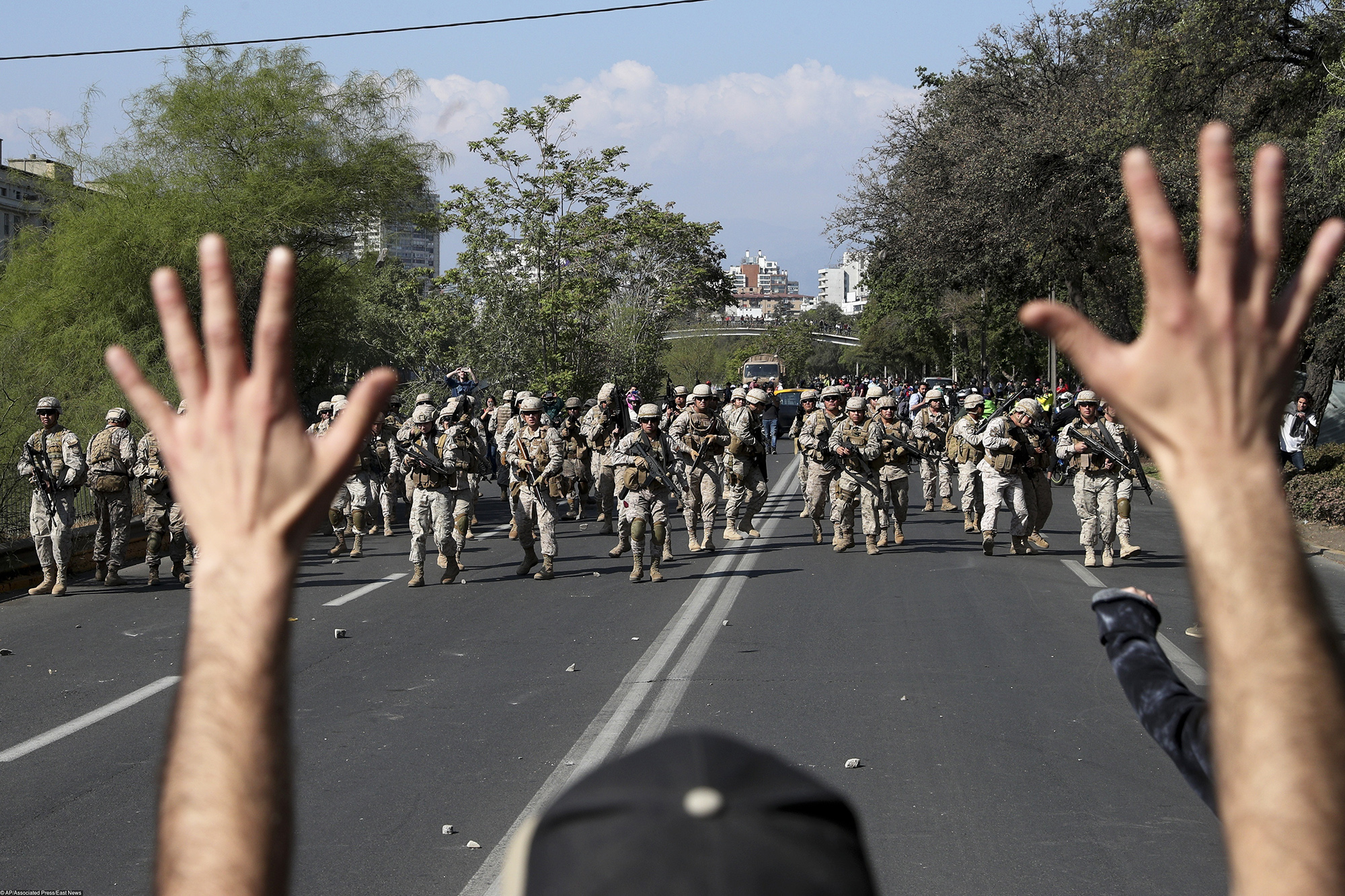 A demonstrator holds up his hands toward advancing soldiers as a state of emergency remains in effect in Santiago, Chile, Sunday, Oct. 20, 2019. Protests in the country have spilled over into a new day, even after President Sebastian Pinera cancelled the subway fare hike that prompted massive and violent demonstrations