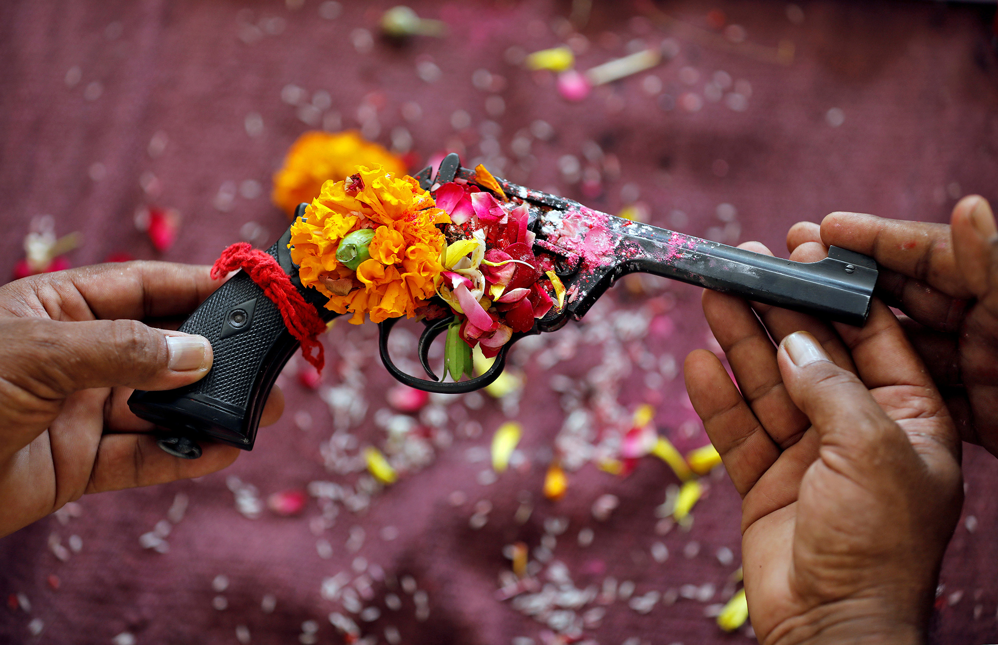 Police officers hold a revolver as they offer prayers to their weapons as part of a ritual at their headquarters on the occasion of Dussehra, or Vijaya Dashami, festival in Ahmedabad, India, October 8, 2019. REUTERS/Amit Dave TPX IMAGES OF THE DAY