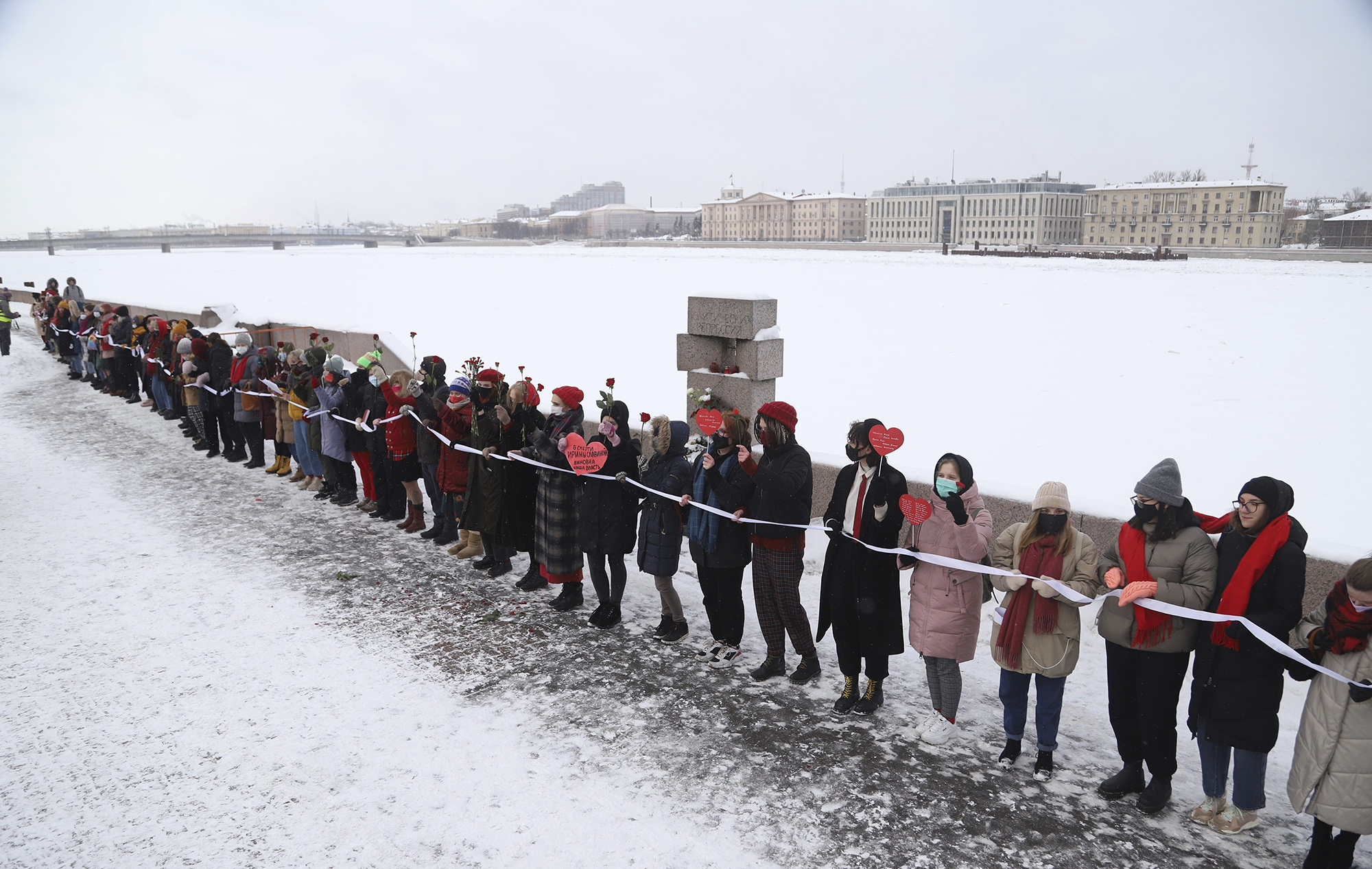 Women, some of them wearing face masks to protect against coronavirus, attend a rally in support of jailed opposition leader Alexei Navalny and his wife Yulia Navalnaya, in St. Petersburg, Russia, Sunday, Feb. 14, 2021. Participants formed a human chain in a show of solidarity with those who were detained during protests calling for the release of jailed Russian opposition leader Alexei Navalny, and the Kremlin has accused the West of meddling in Russia's affairs by denouncing the crackdown on protests. (AP Photo/Ivan Petrov)