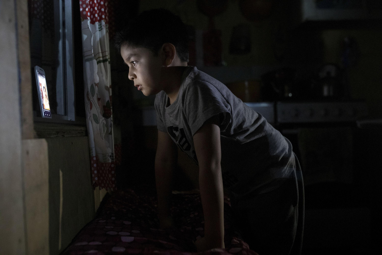 7-летний Диего Герреро смотрит видео намобильном телефоне со слабым интернет-сигналом, который доходит додома вдеревне Сотомо, недалеко отгорода Кочамо, регион Лос-Лагос, Чили, 8 августа