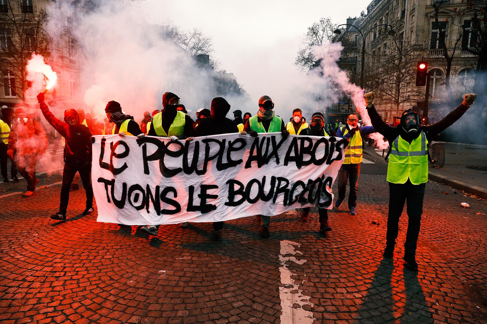Протестующие вжелтых жилетах используют дымовую шашку наЕлисейских полях
