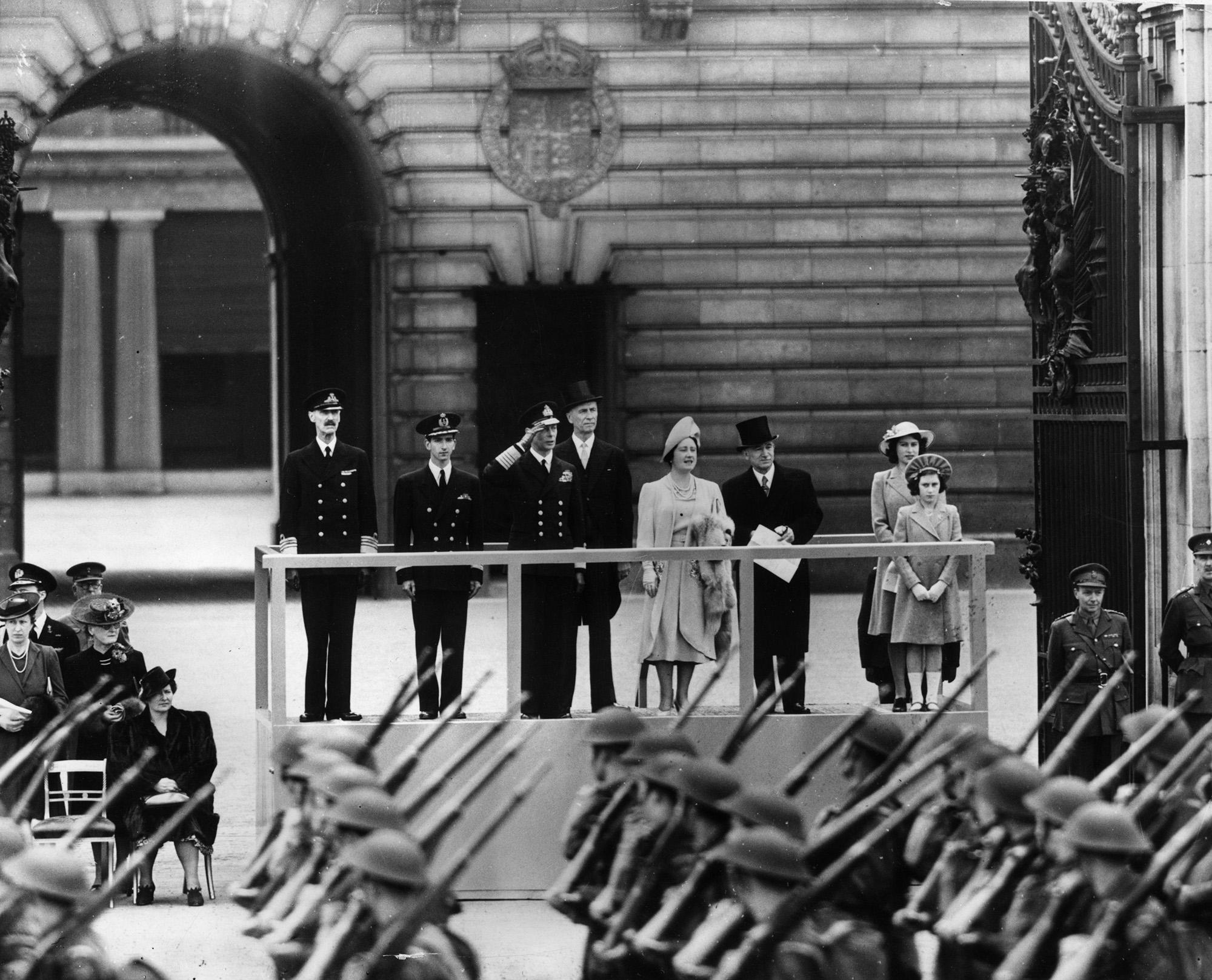 Король Георг VI принимает парад уБукингемского дворца вместе со своими дочерями Елизаветой иМаргарет.