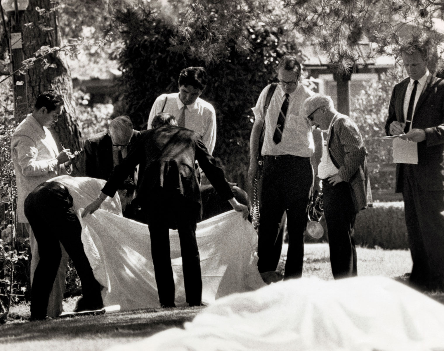 County Coroner Thomas Nogouchi (left) takes notes as assistants hold sheet which covered one body as the other of the two bodies found on the lawn of the Sharon Tate-Roman Polanski home shows in foreground. Five persons were discovered murdered on the property early August 9th, the work of the Manson Family.