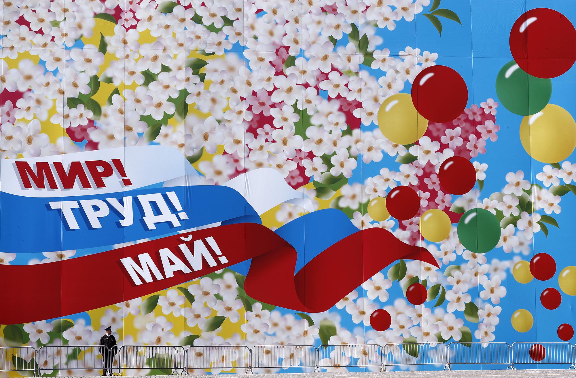 Полицейский стоит передогромным плакатом снадписью «Мир, труд, май» во время празднования Дня труда наКрасной площади. Москва, Россия, 1 мая 2019 года. День труда во всем мире — повод отметить экономические исоциальные достижения трудящихся.