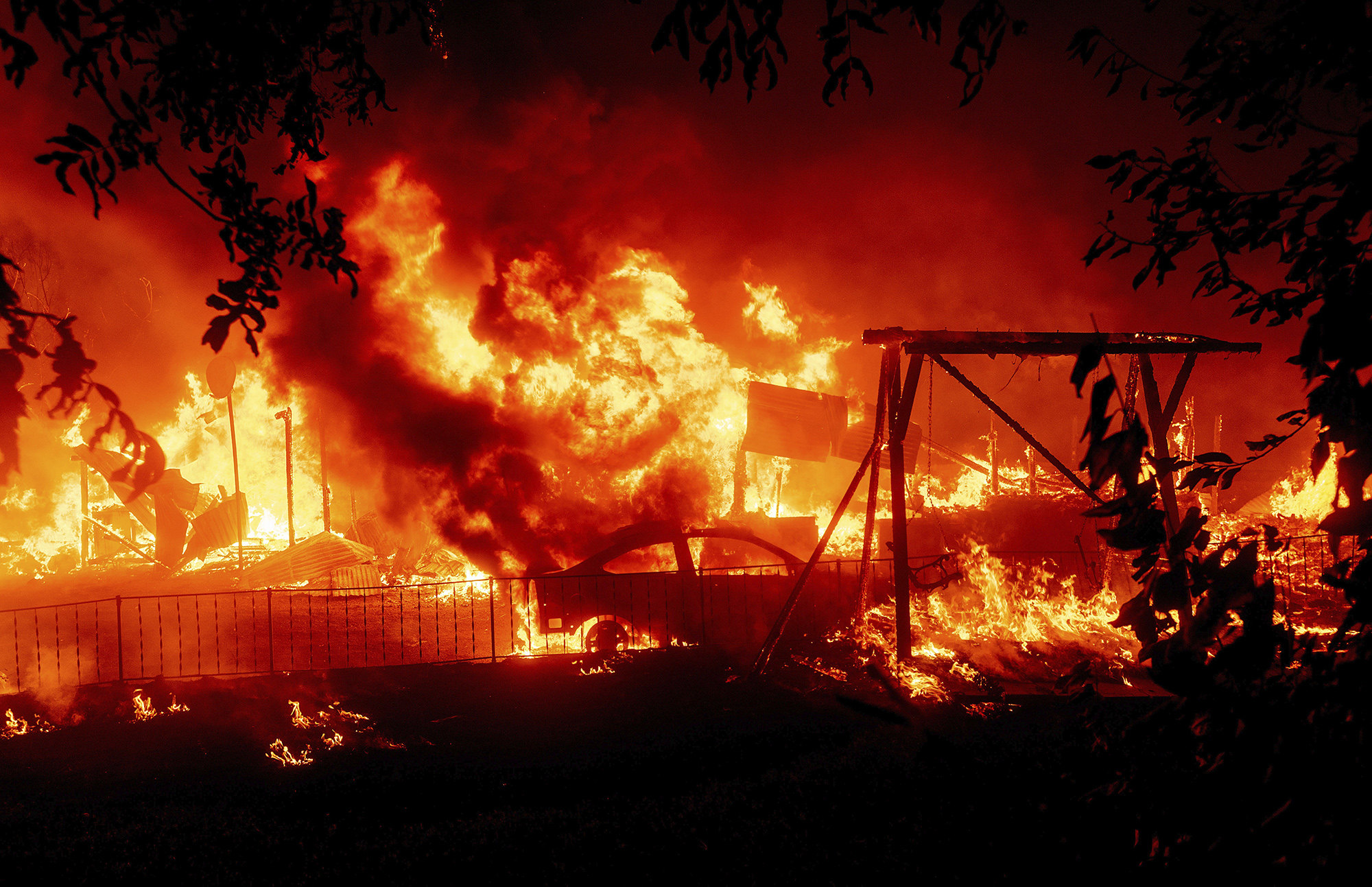 Flames consume a home and car as the Bear Fire burns through the Berry Creek area of Butte County, Calif., on Wednesday, Sept. 9, 2020. The blaze, part of the lightning-sparked North Complex, expanded at a critical rate of spread as winds buffeted the region. (AP Photo/Noah Berger)