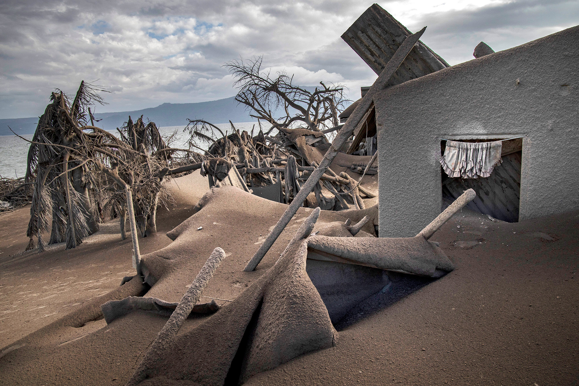 TAAL VOLCANO ISLAND, PHILIPPINES - JANUARY 14: Houses near Taal Volcano's crater are seen buried in volcanic ash from the volcano's eruption on January 14, 2020 in Taal Volcano Island, Batangas province, Philippines. The Philippine Institute of Volcanology and Seismology raised the alert level to four out of five, warning that a hazardous eruption could take place anytime, as authorities have evacuated tens of thousands of people from the area. An estimated $10 million worth of crops and livestock have been damaged by the on-going eruption, according to the country's agriculture department. (Photo by Ezra Acayan/Getty Images)