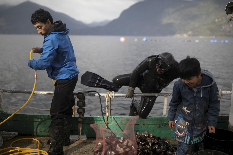 37-летний Патрисио Герреро скручивает кислородный шланг, пока его 40-летний брат Карлос Герреро забирается влодку после снорклинга вустье реки Релонкави вдеревне Сотомо, недалеко отгорода Кочамо, регион Лос-Лагос. Чили, 7 августа 2021 года.