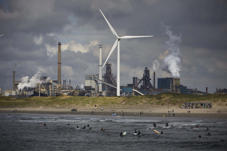 Серферы нафоне сталелитейного Tata Steel, угрожающего окружающей среде, пирса 20 августа 2021 года вВелсен-Ноорде. Сталелитейный завод Tata находится подследствием голландской