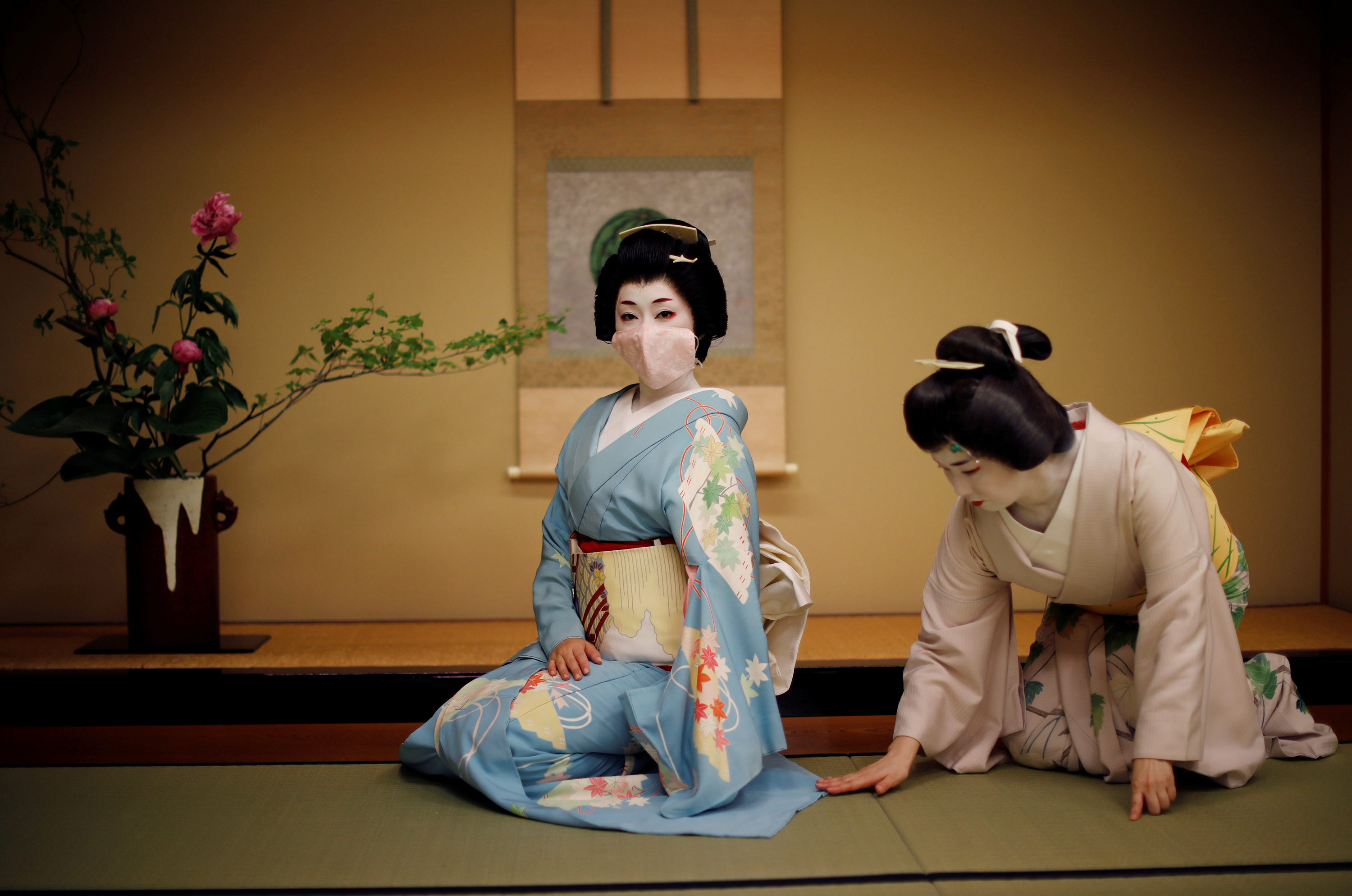 Mayu adjusts Koiku's kimono, both of who are geisha, as Koiku wears a protective face mask to pose for a photograph, before working at a party being hosted by customers, where they will entertain with other geisha, at Asada, a luxury Japanese restaurant, during the coronavirus (COVID-19) outbreak, in Tokyo, Japan, June 23, 2020.